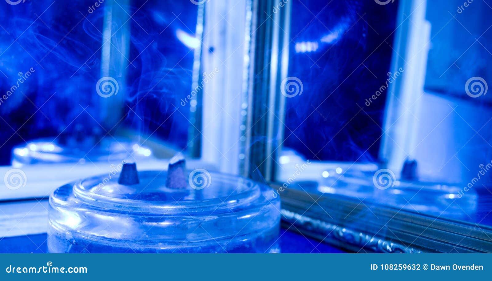 Humo del incienso reflejado en dos espejos