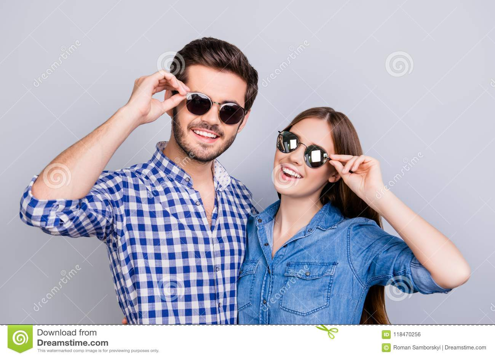 Humor del verano y de la diversión Los estudiantes jovenes están llevando las gafas de sol de moda y sonrisa, en las camisas spor