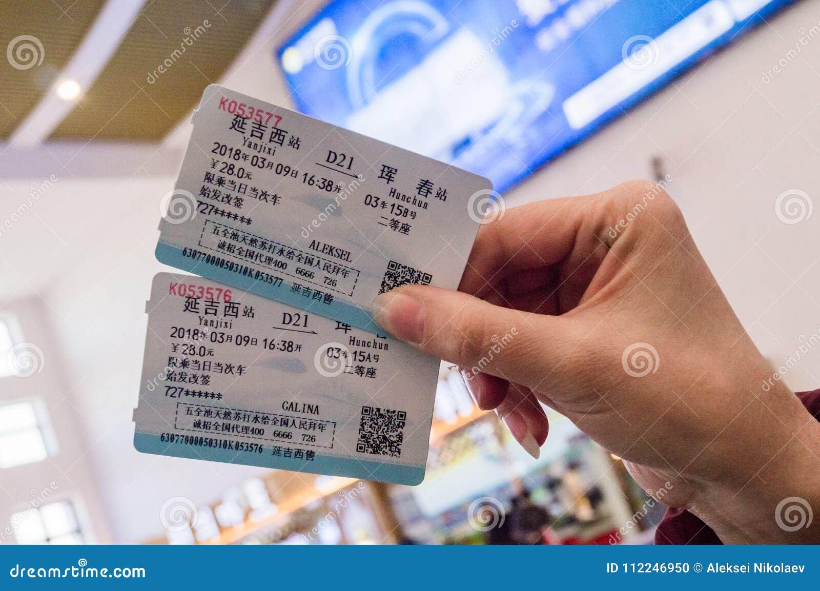 HUNCHUN, JILIN CHINY, Marzec, - 8, 2018: Dwa bileta w kobiety ` s ręce dla podróży szybkościowym pociągiem CRH