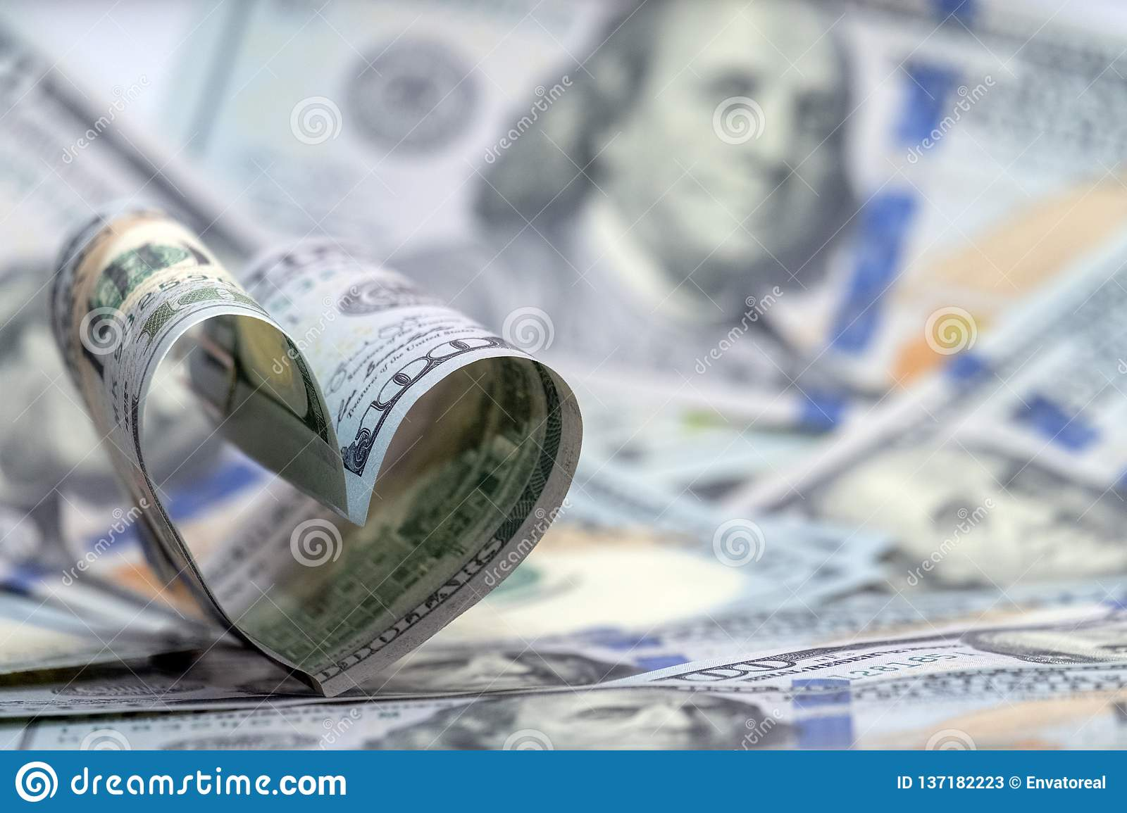 Hundred dollar banknote of usa in the shape of a heart. Money background. Concept financial love and a gift for Valentine`s Day.
