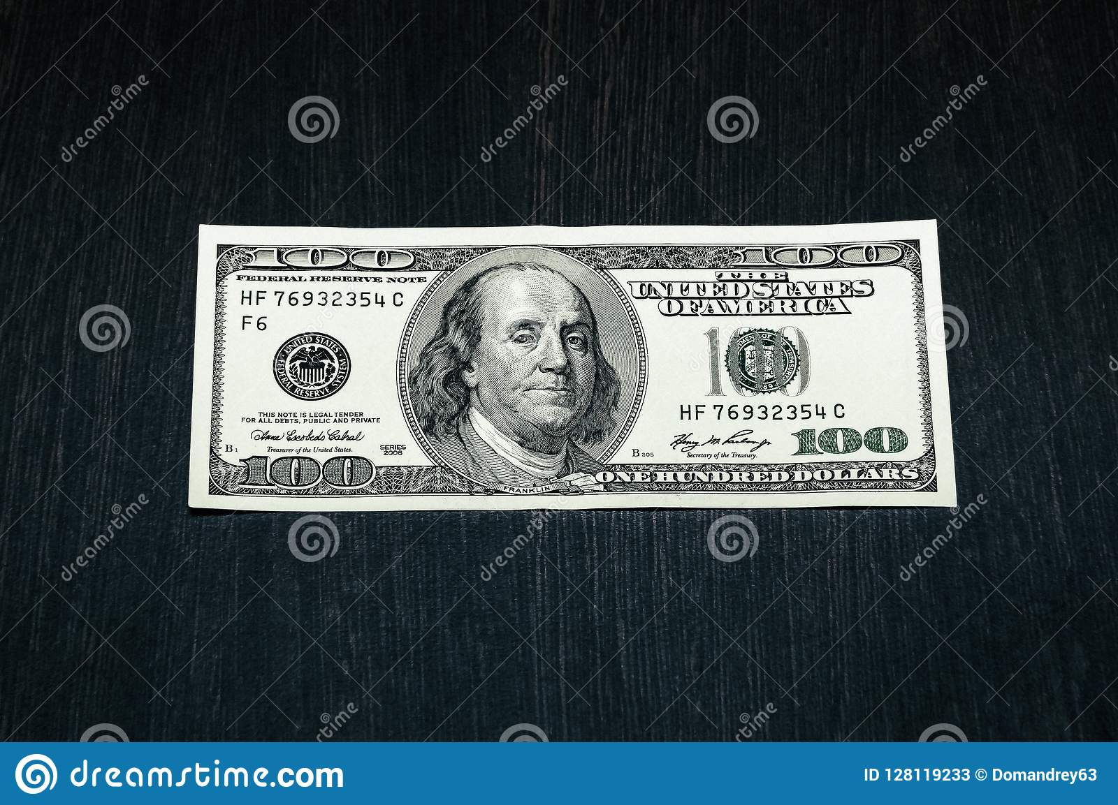 A Hundred Dollar Bill On A Table Made Of Dark Textured Wood