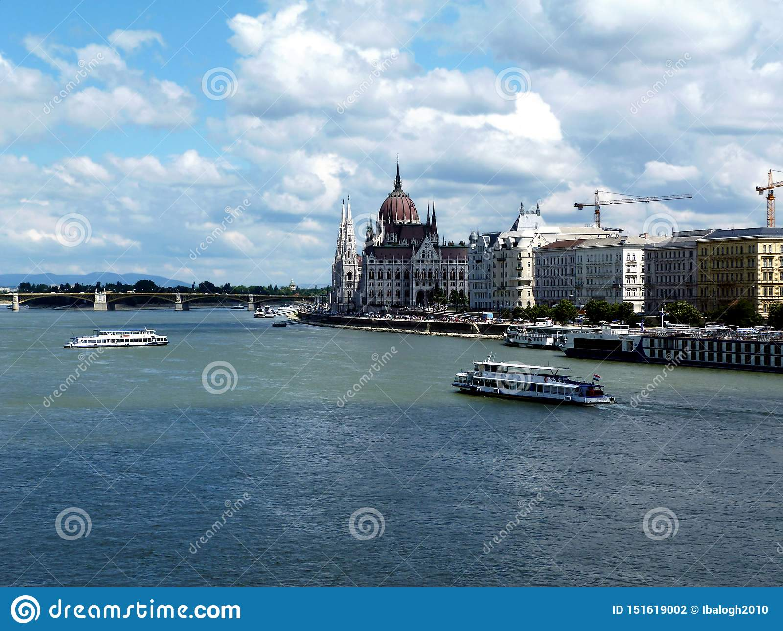Hungarian Parliament and the Danube in panoramic landscape with white tour boats