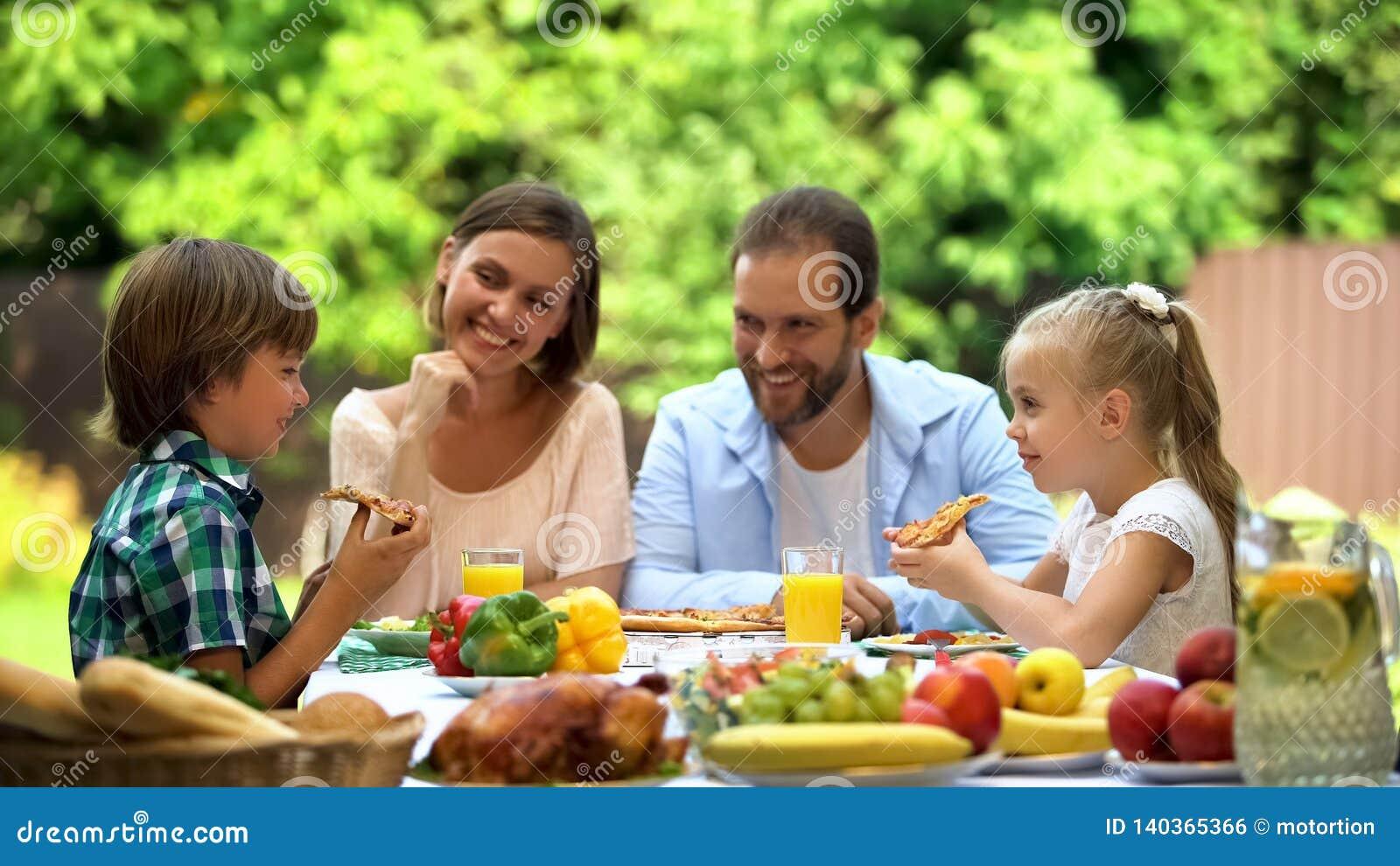 Hungriga ungar som äter läcker pizza, barns favorit- mat, italiensk kokkonst