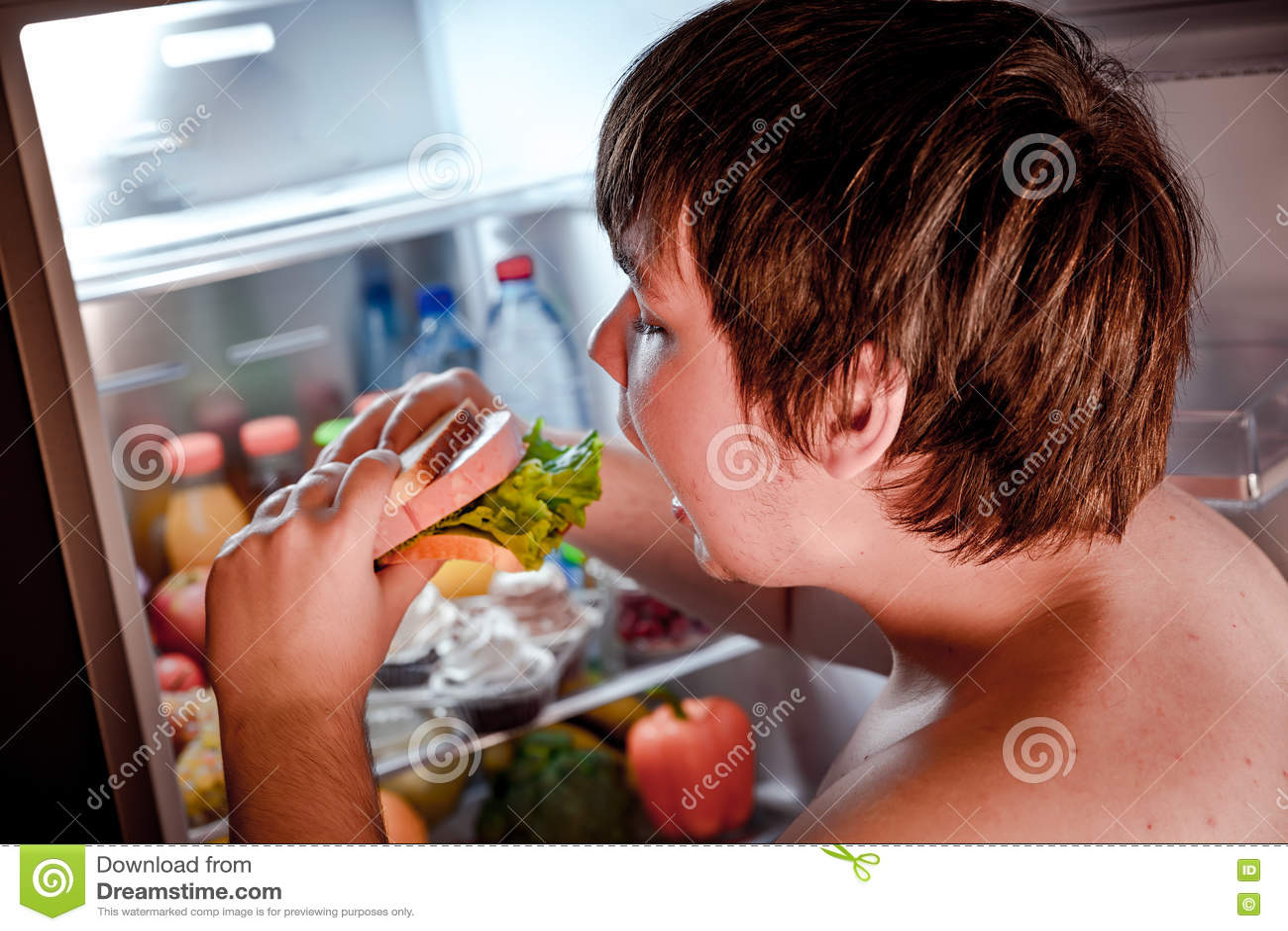 Hungriger Mann, der ein Sandwich in seinen Händen und in Stellung nahe bei hält