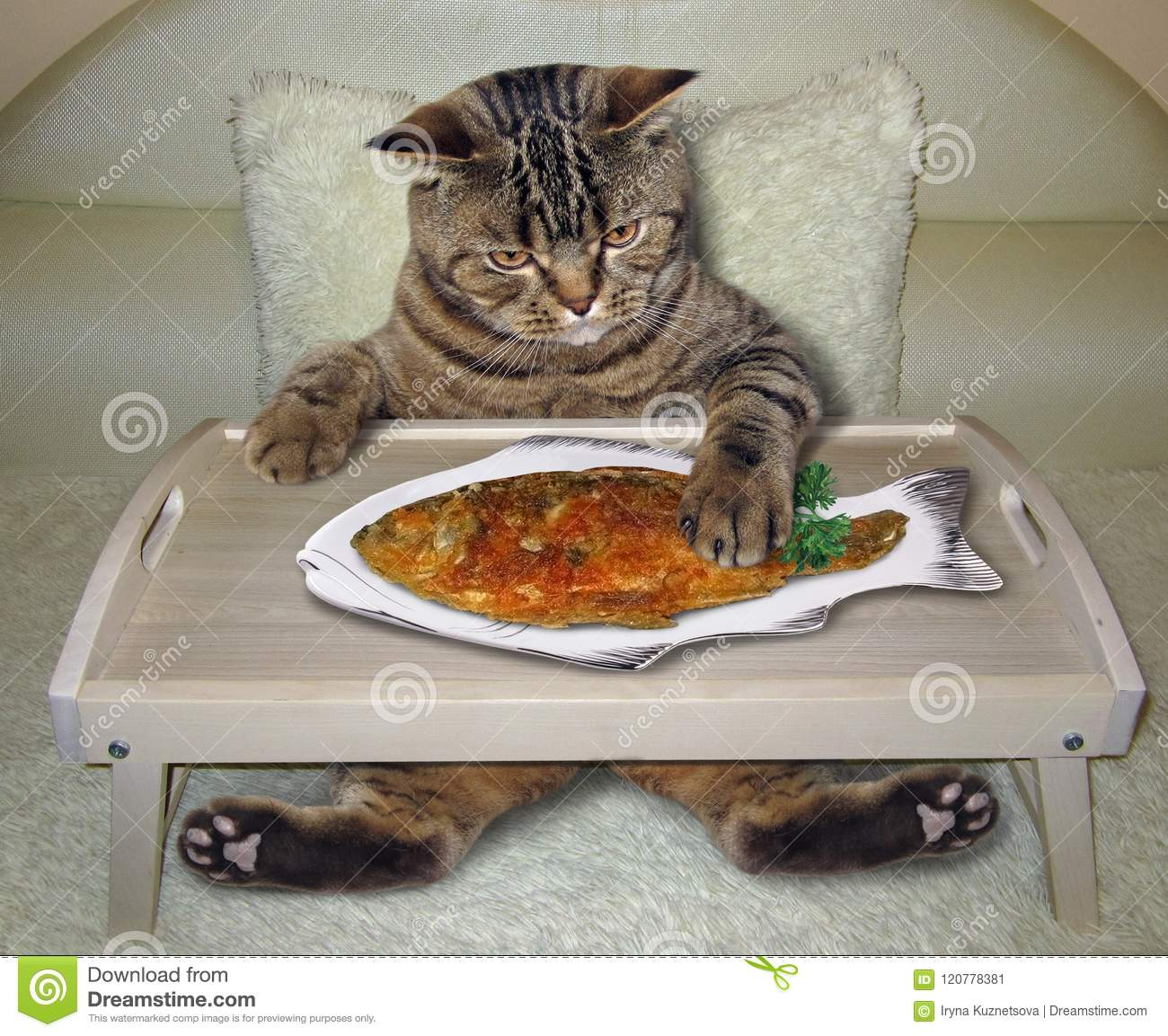 Cat eats fried fish on the bed