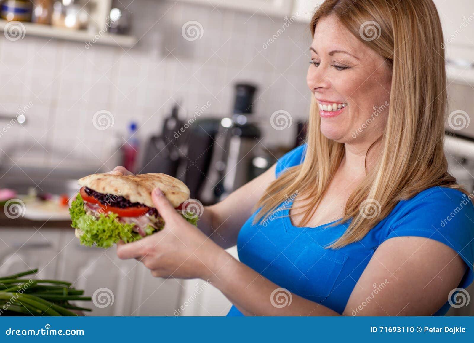 hungry pregnant woman eating a big burgerjunk food stock