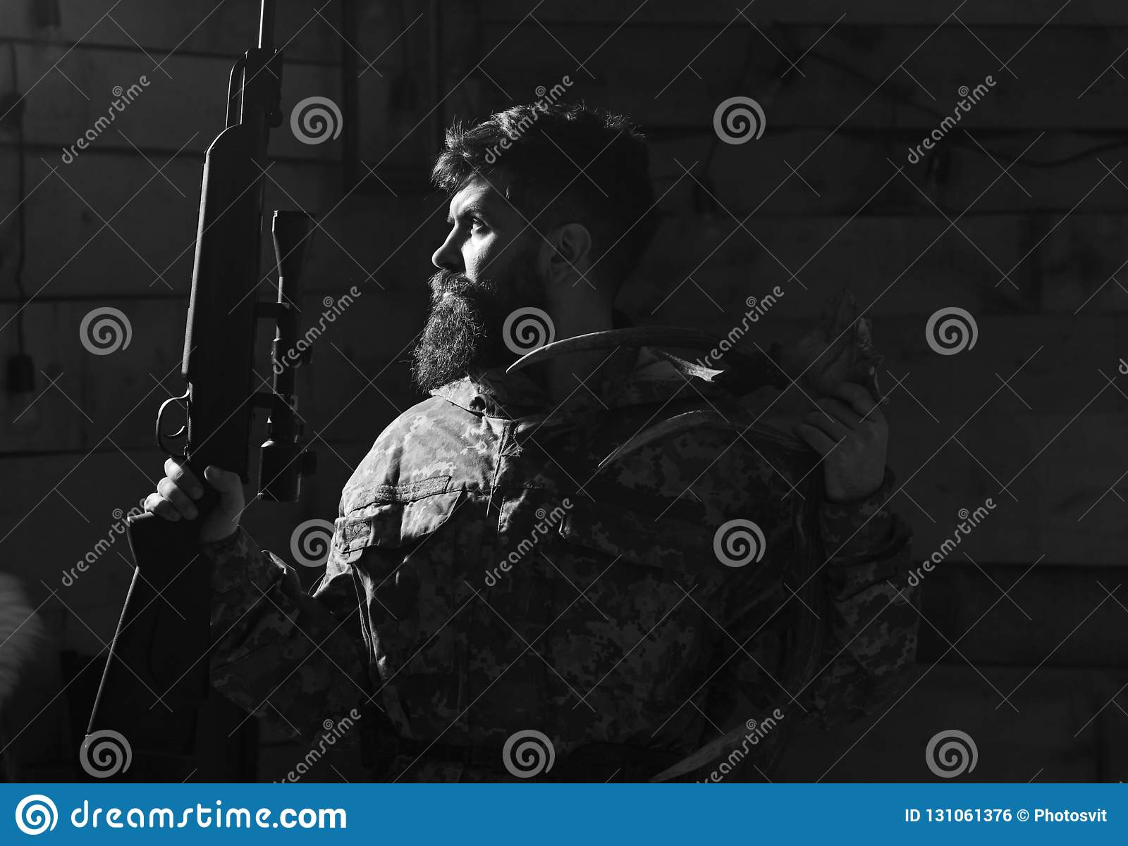 Hunter concept. Portrait of bearded modern hunter with his trophy holds rifle. Man with beard wears camouflage clothing