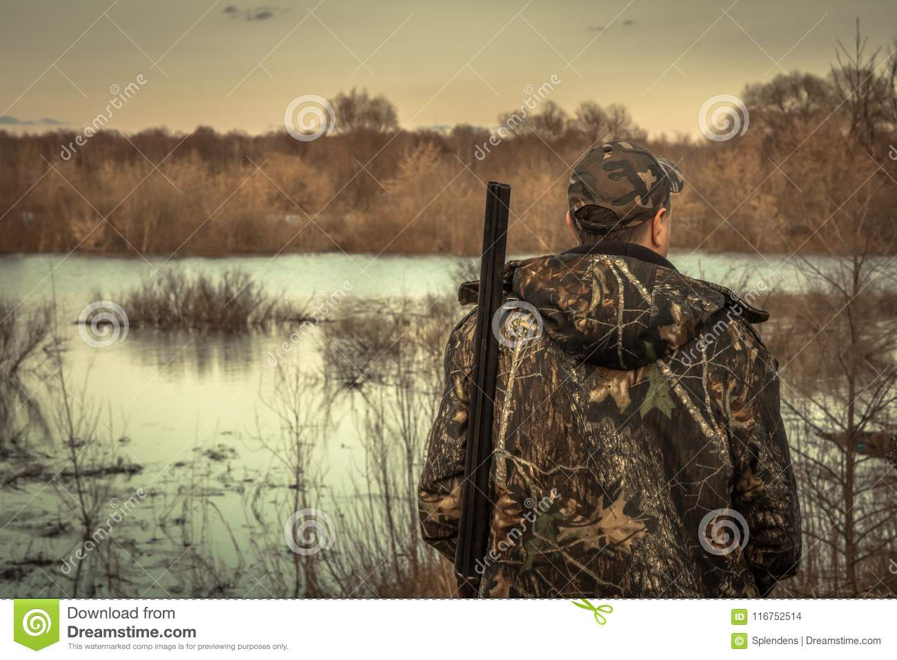 Hunter man shotgun camouflage exploring flood river hunting season rear view sunset