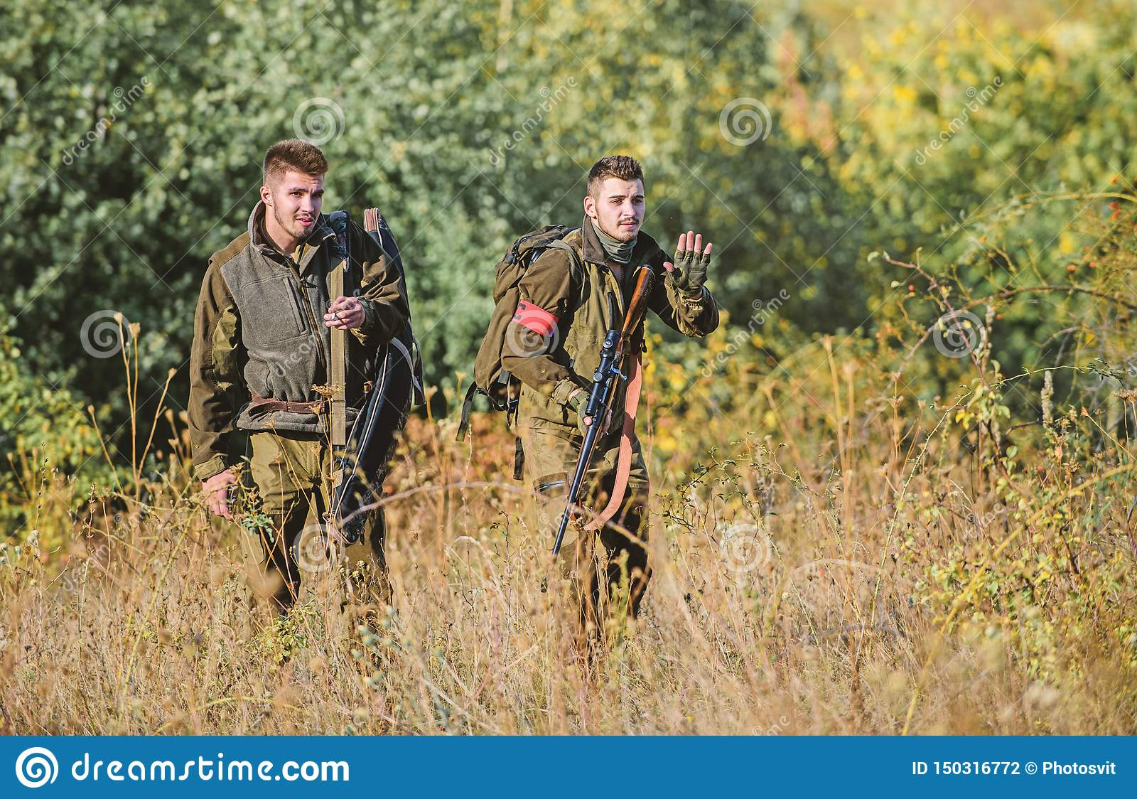 Hunting with friends. Hunters friends enjoy leisure. Hunters with rifles in nature environment. Teamwork and support