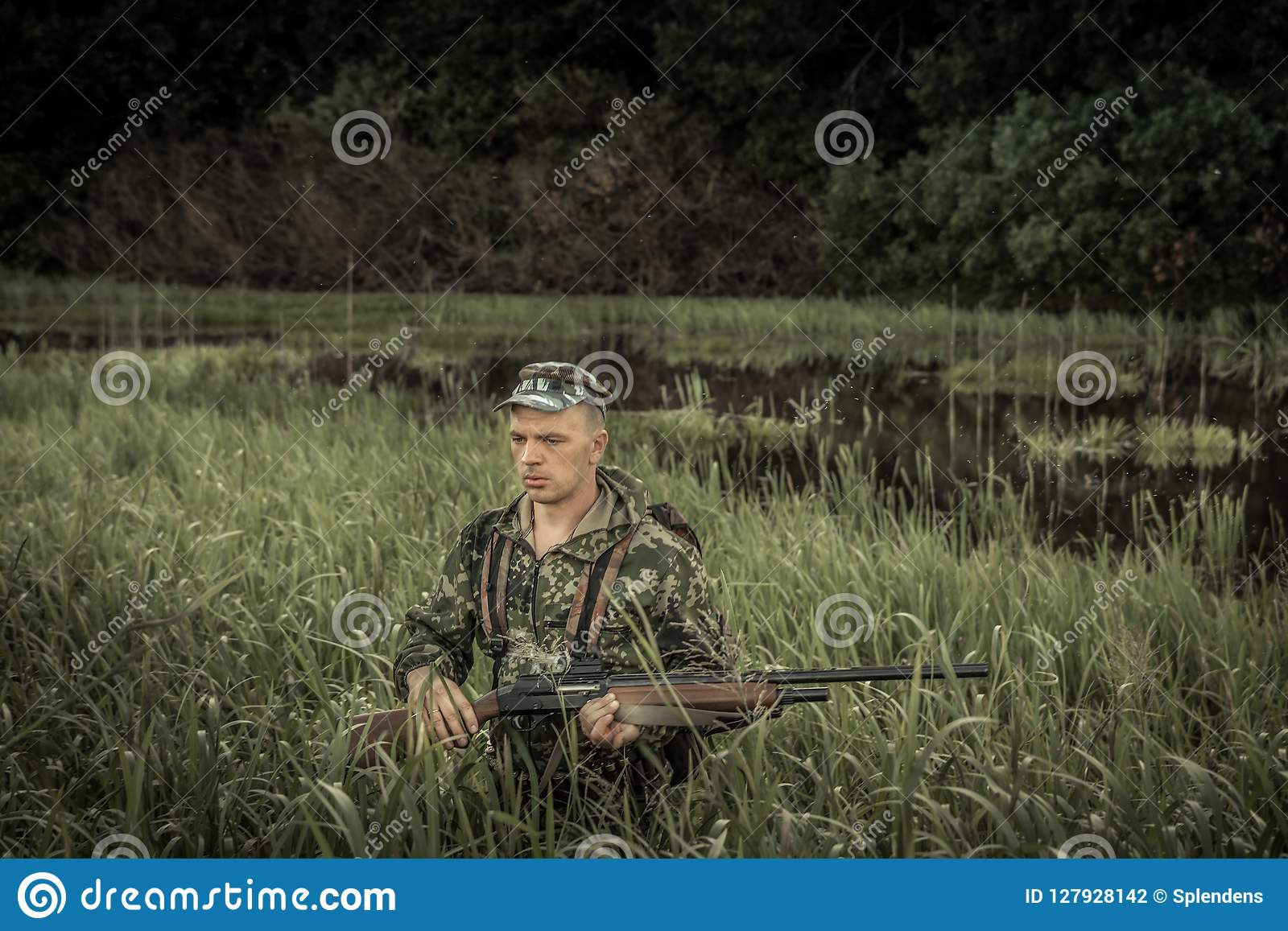 Hunting hunter brutal man breaking through swamp tall grass during hunting season