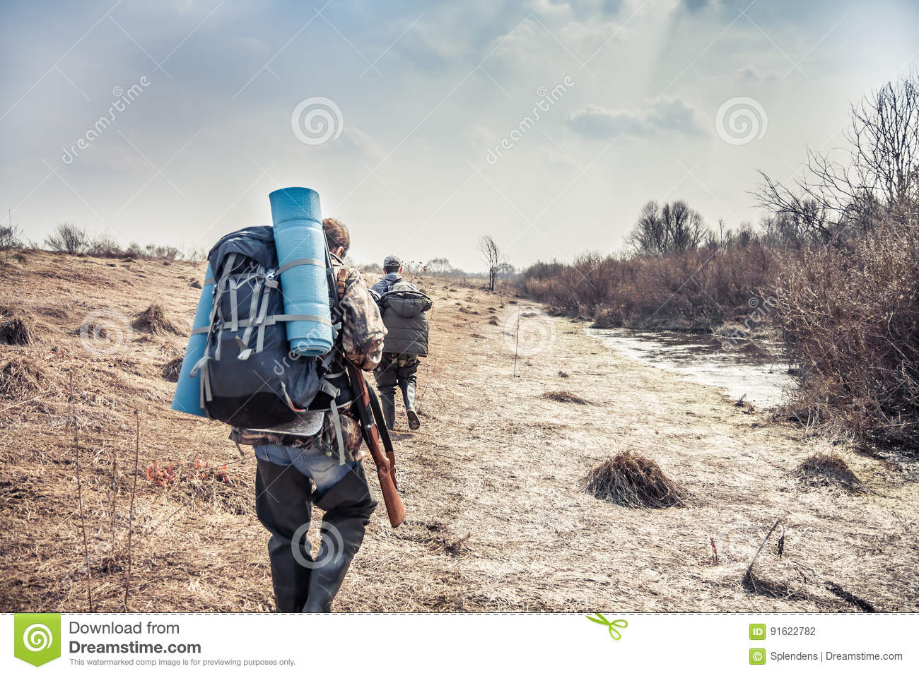 Hunting scene with hunters with backpack and hunting equipment going across rural area during hunting season
