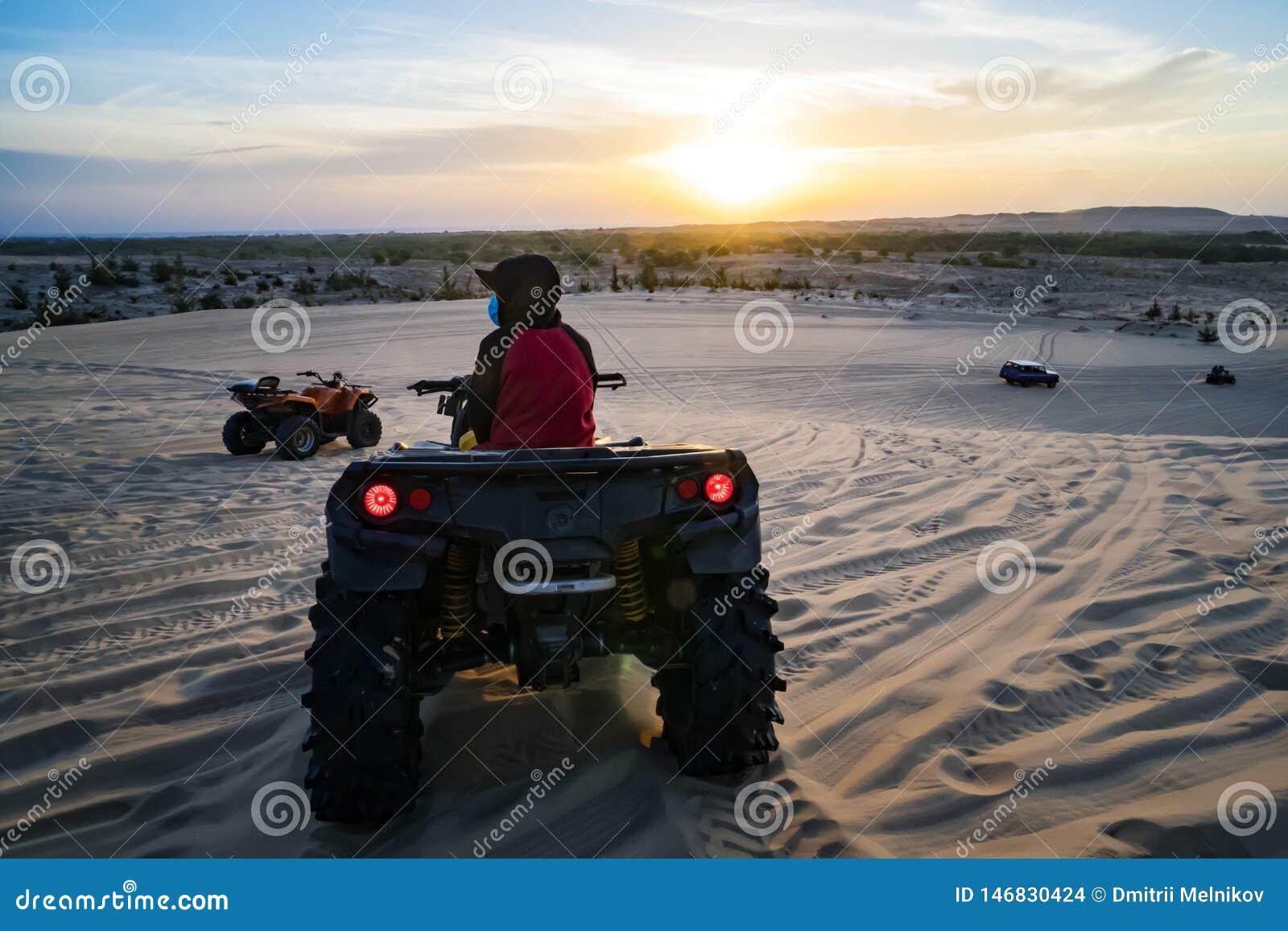Hurghada, Ägypten - 10. Dezember 2018: Junger Mann in der Safarireise durch die ägyptische Wüste, die ATV bei Sonnenuntergang fäh