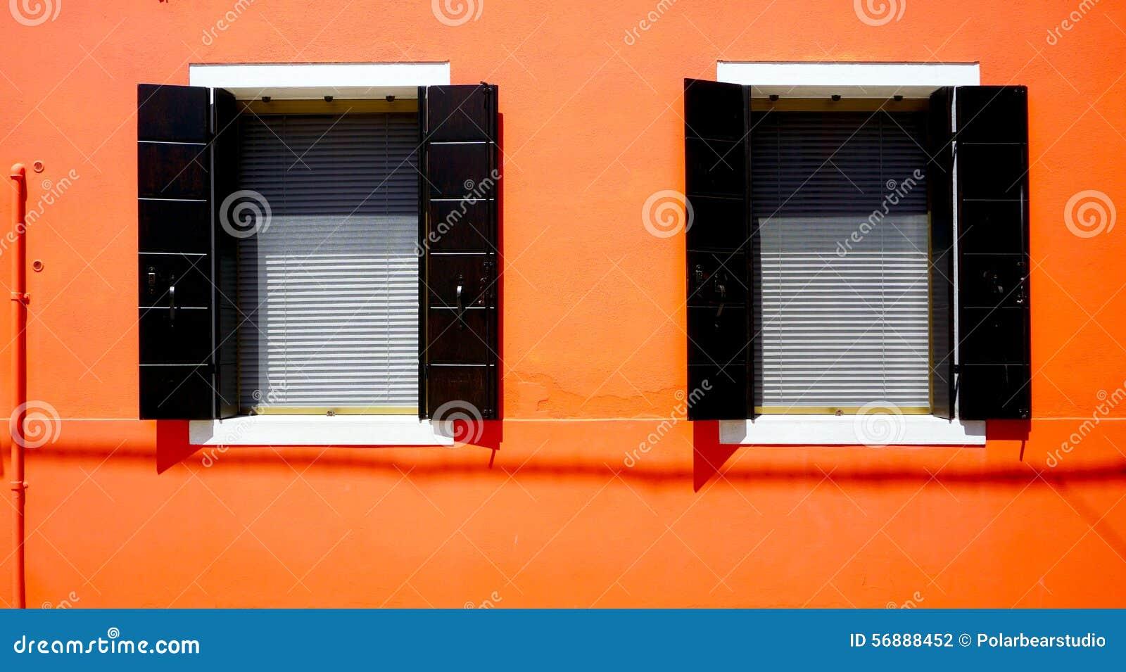 Hus för två Windows i Burano på den orange väggen