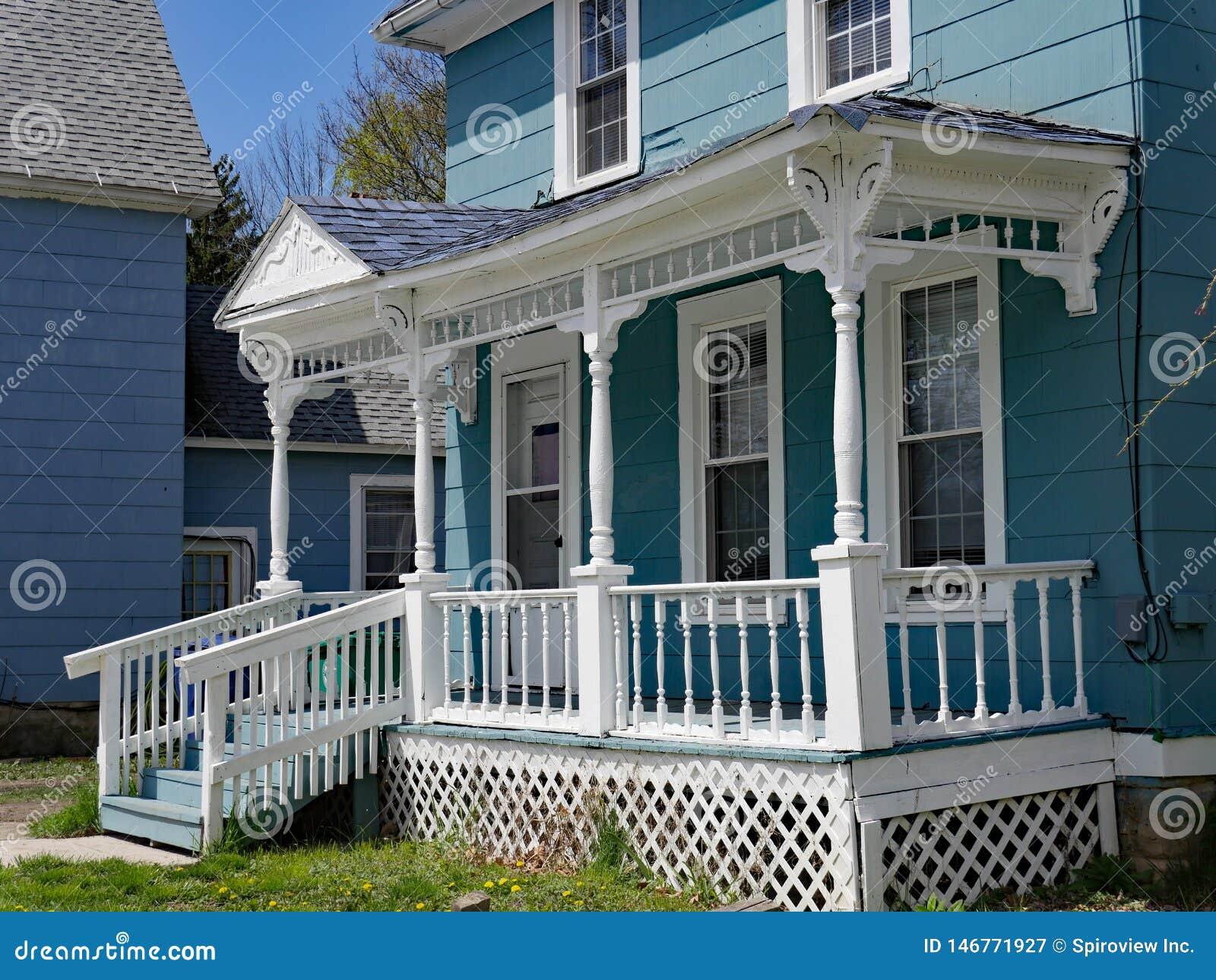 Hus med den gammalmodiga träspindelräcket på farstubron