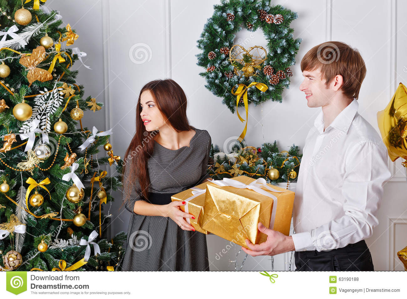 Husband Gives His Wife A Gift For Christmas Stock Photo