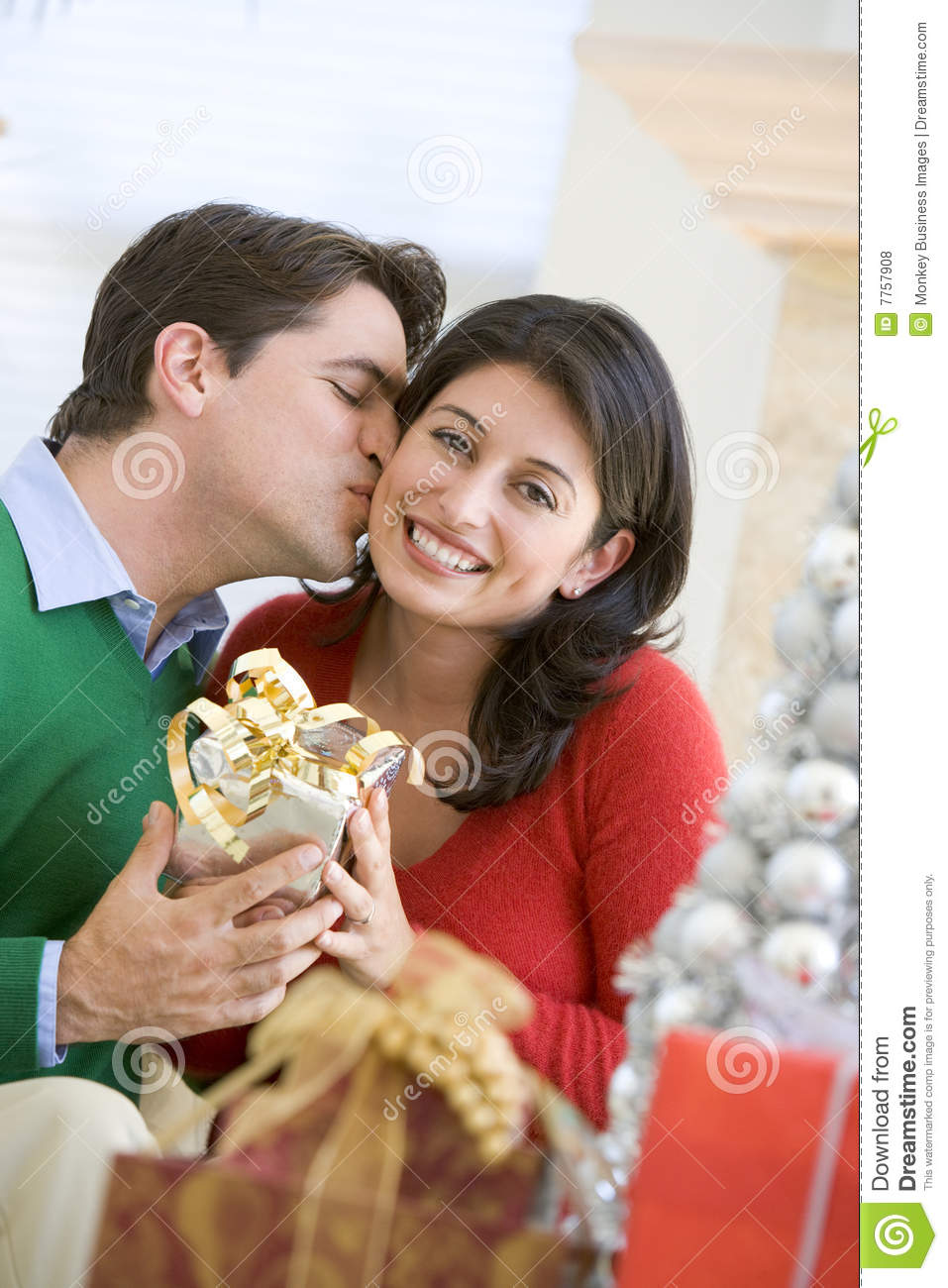 Husband Surprising Wife With Christmas Present Stock Photo
