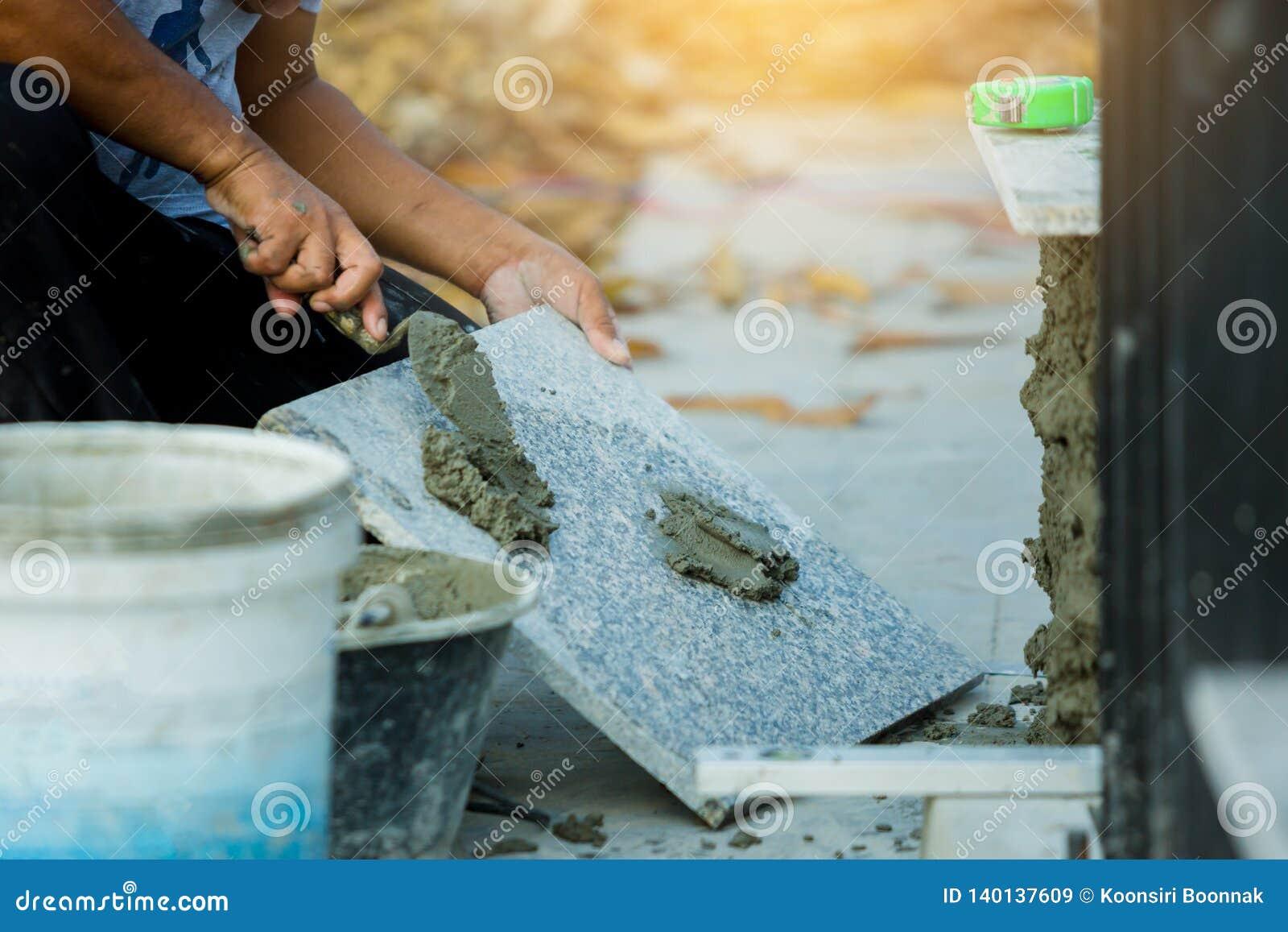 Husförbättring, renovering, arbetare för konstruktionsbransch som installerar granitstentegelplattor med cement
