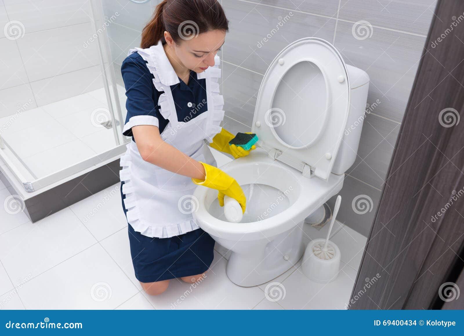 Hushållerska som skurar ner toalett i badrum arkivfoto   bild ...