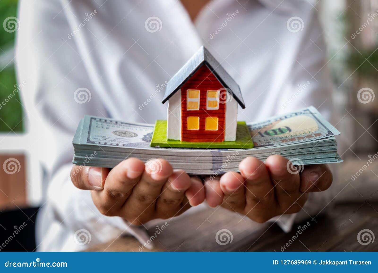 Husmodell och pengar i hand