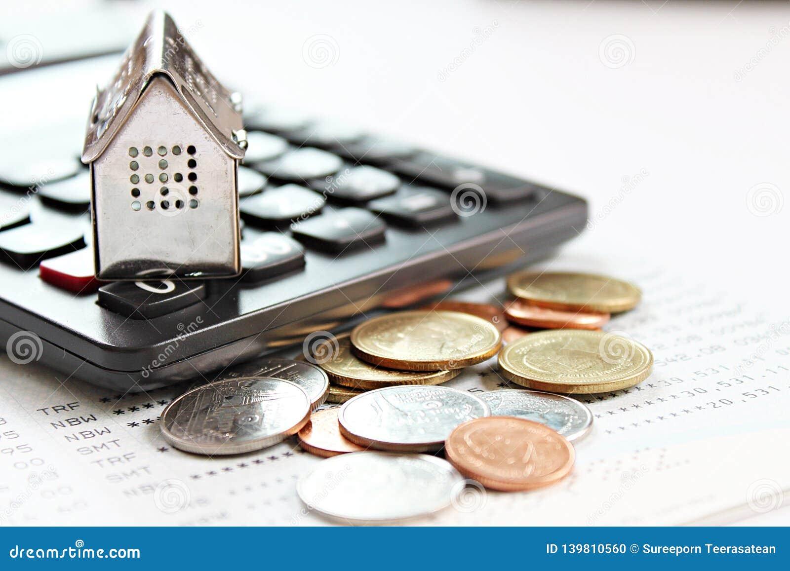 Husmodell, räknemaskin och mynt på sparkontobankbok eller bokföringsunderlag