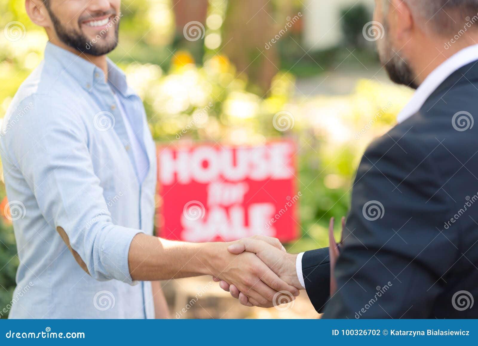 Hussäljare som skakar handen för köpare` s