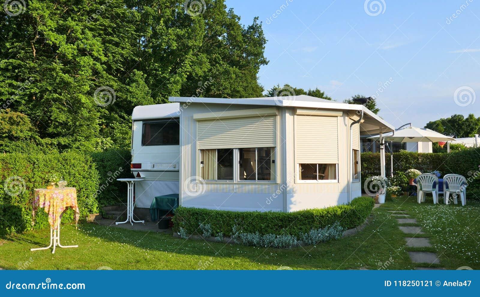 Husvagn med en fast veranda som göras av markistyg, glass glidningsfönster och rullgardiner på en tysk campingplats