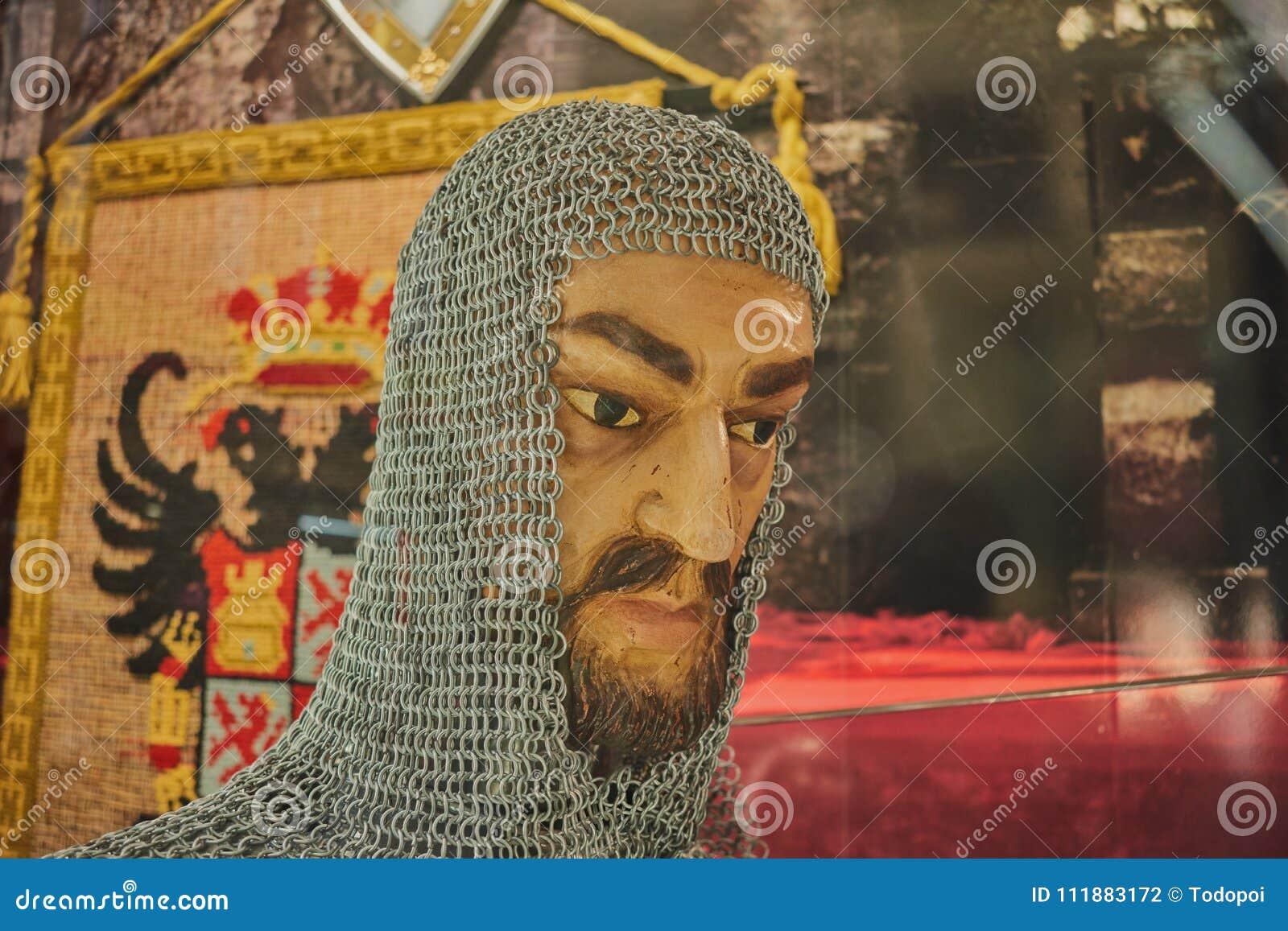 Huvud av den forntida mannen med skägget som täckas av ingreppet av cirklar för skydd med en gammal standert i bakgrunden i Toled