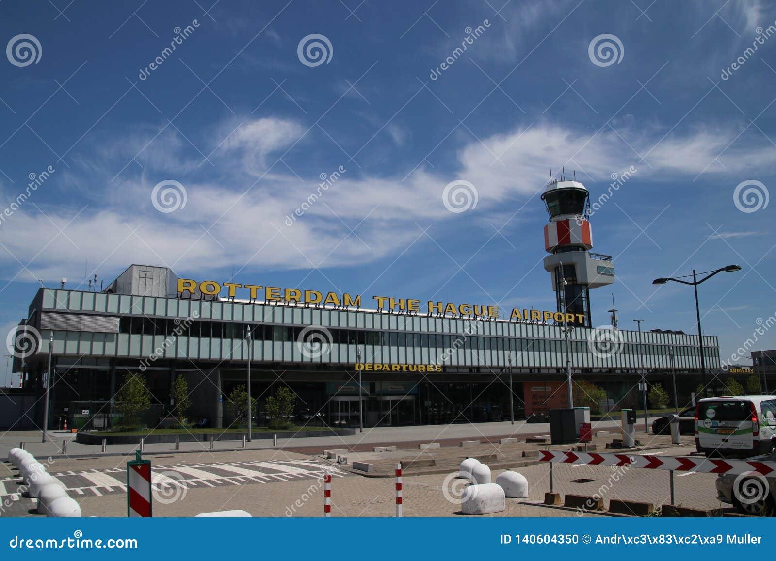 Huvudbyggnad för ankomster och avvikelse av den Rotterdam Haag flygplatsen i Nederländerna med trafiktornet