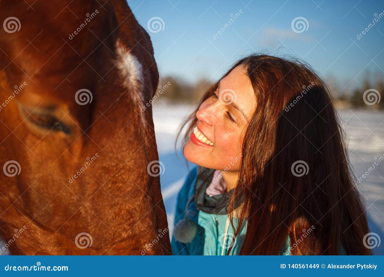 Huvudet av en häst och en flickas händer stänger sig upp Hon matar den röda hästen