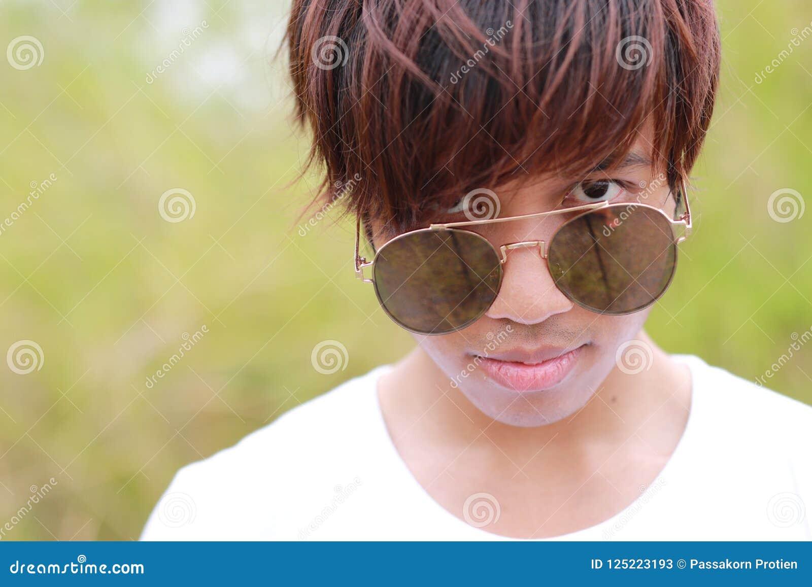 Huvudet som skjutas av thailändsk manlig tonåring i den vit t-skjortan och solglasögon, är stirrigt på kameran