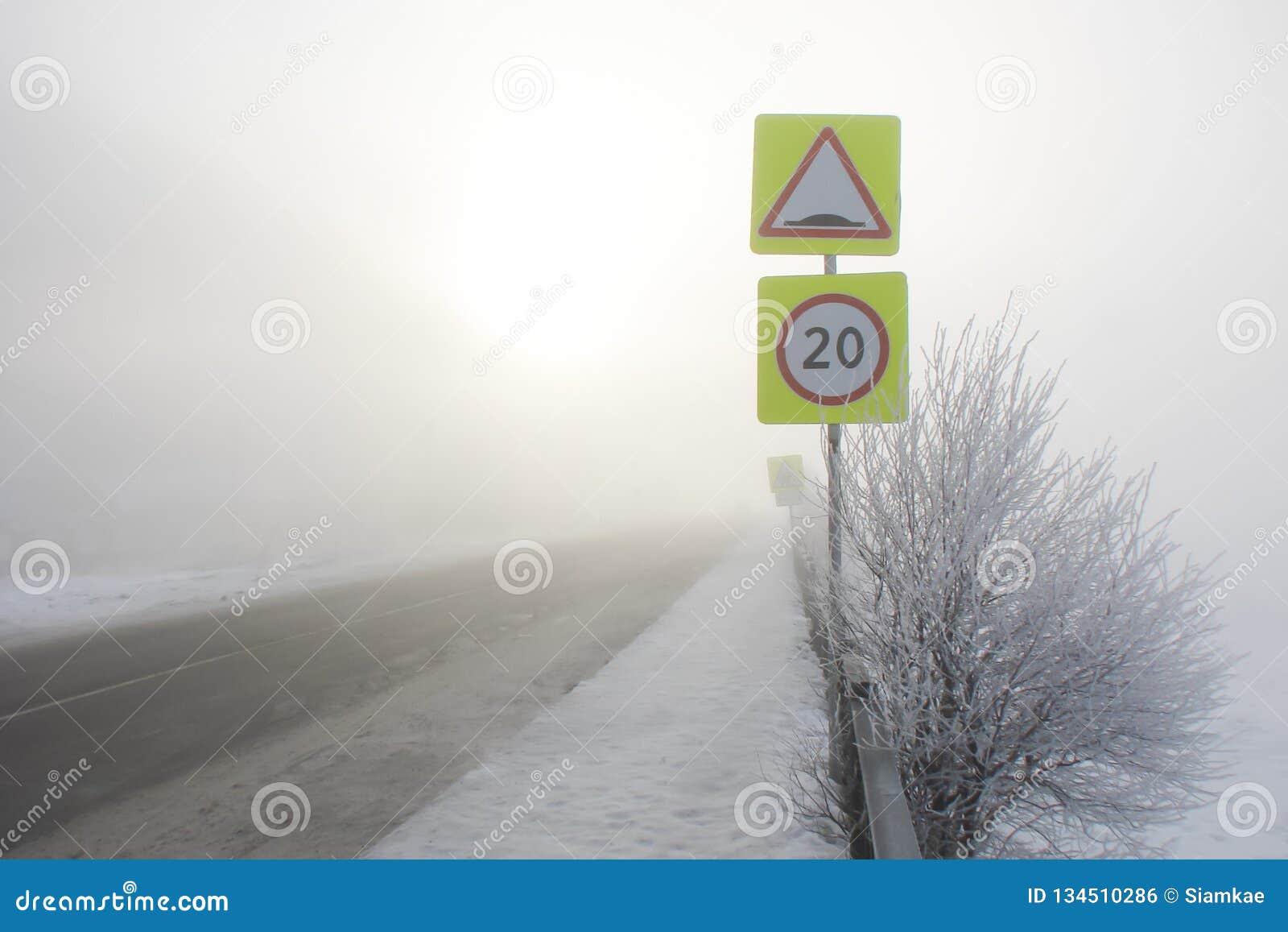 Huvudväg i den dimmiga morgonen i vinter