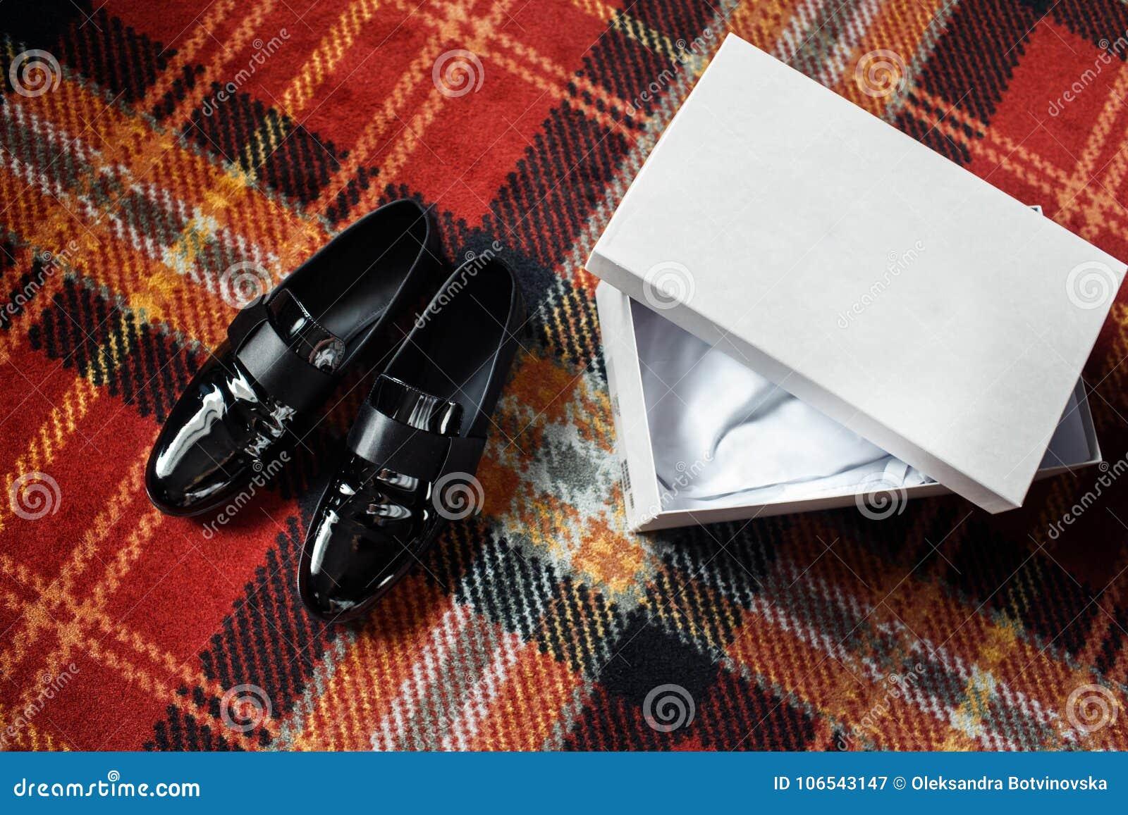 Huwelijks zwarte schoenen en witte doos op de kleurrijke vloer