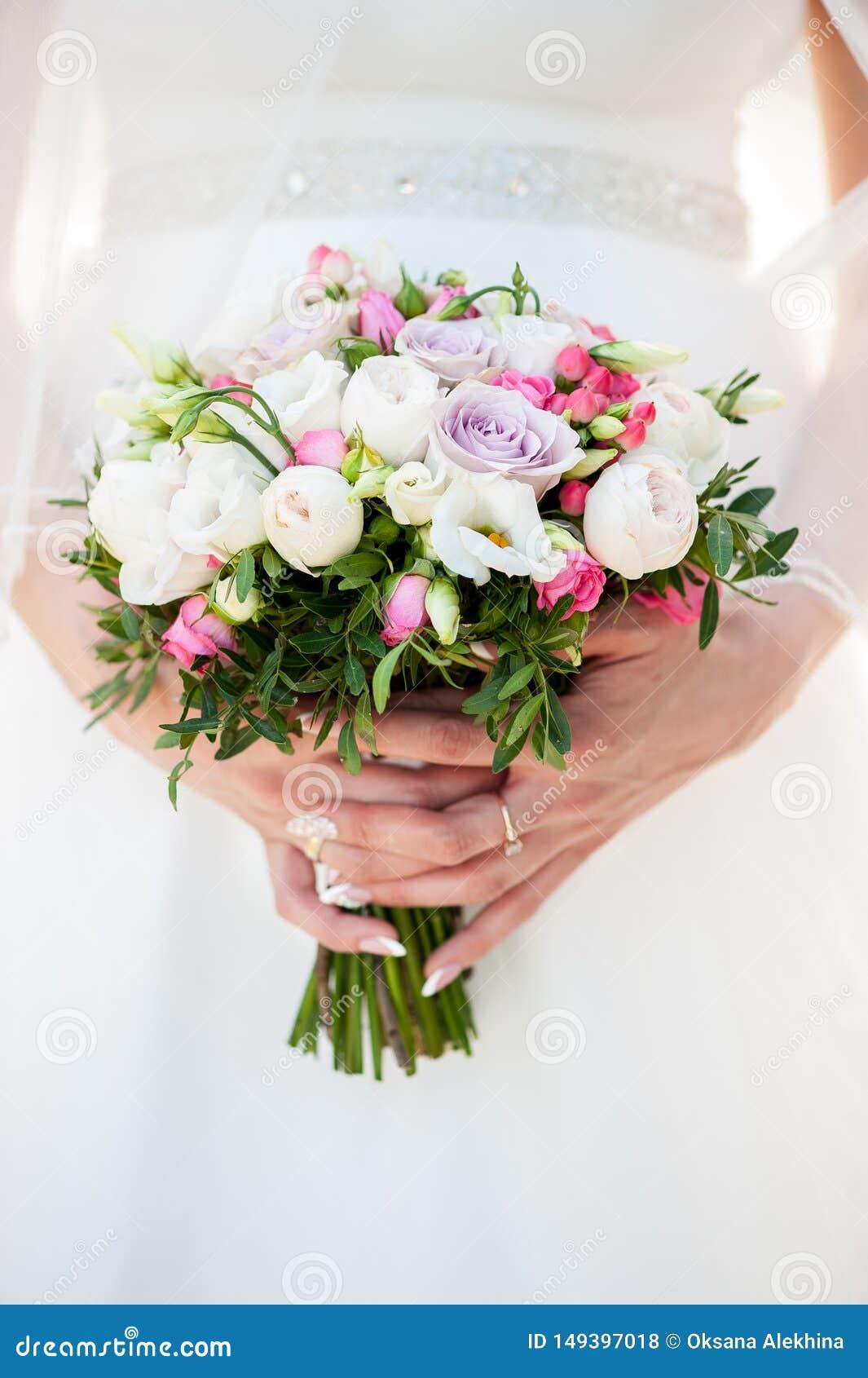 Huwelijksboeket in bruid` s handen