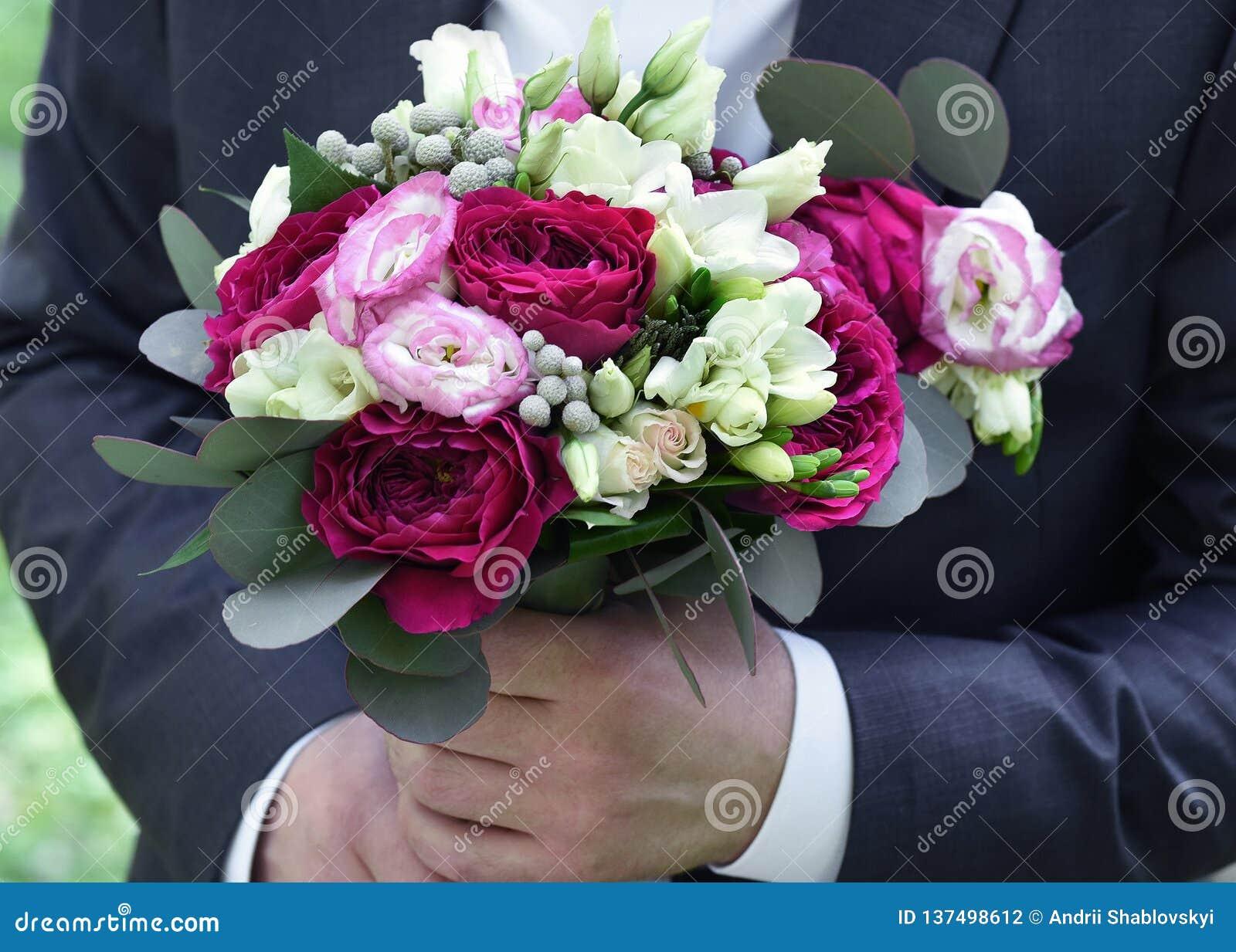 Huwelijksboeket in handen bij de bruidegom De close-up van bloemen