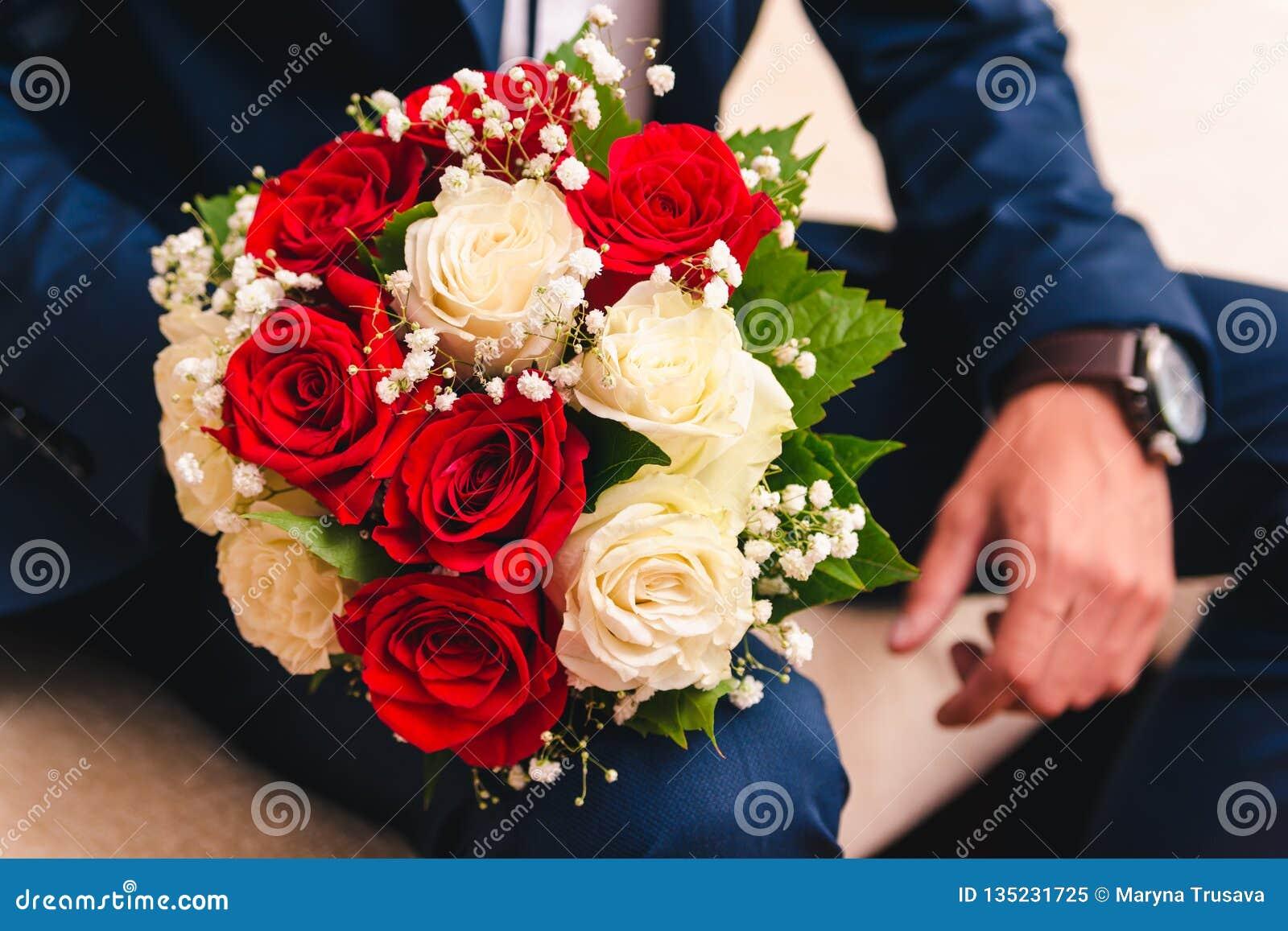 Huwelijksboeket voor de bruid van witte en beige rozen aan de hand van de bruidegom