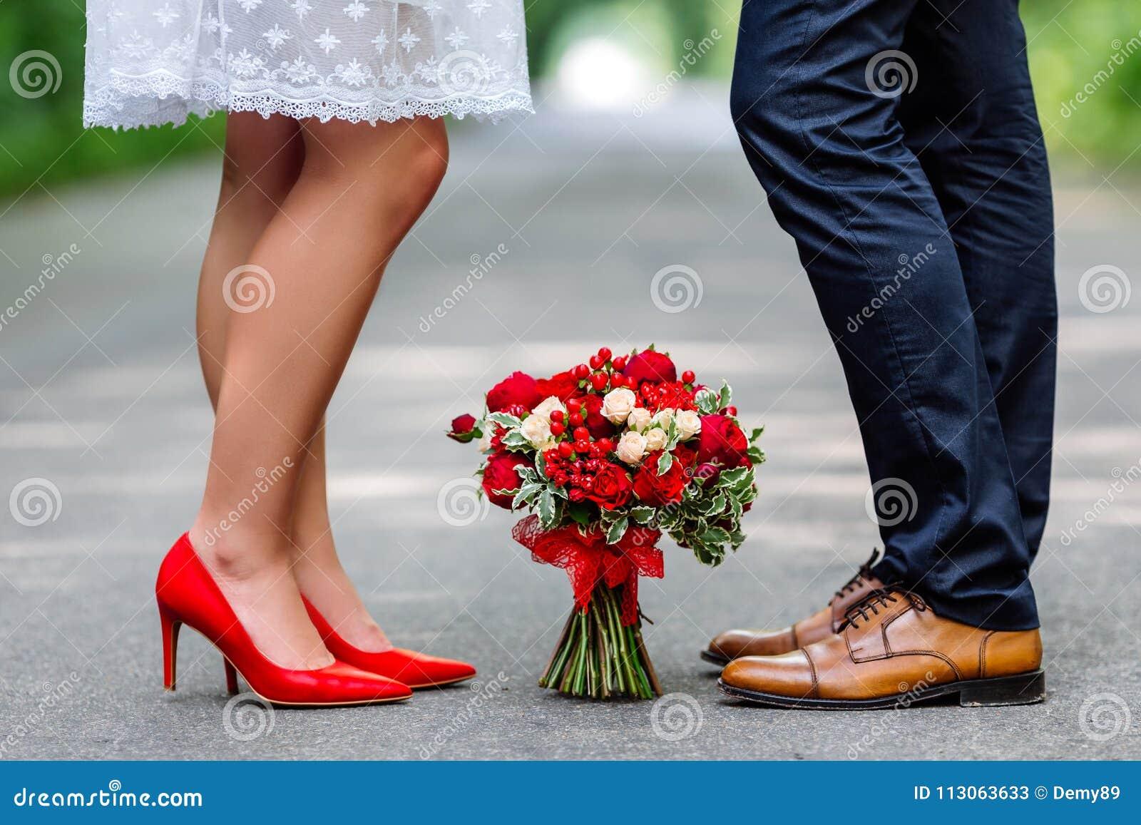 Huwelijksdetails: modieuze rode en bruine schoenen van bruid en bruidegom Boeket van rozen die zich op de grond tussen hen bevind