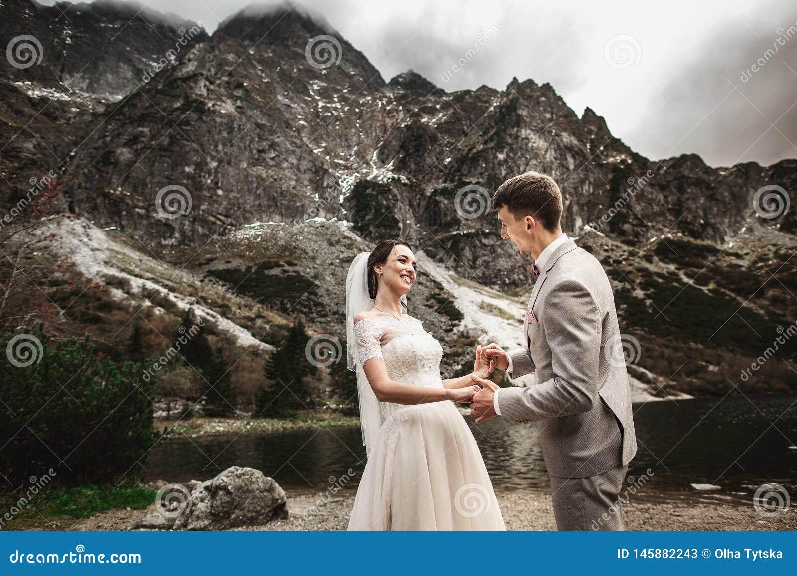 Huwelijkspaar die en handen op de meerkust lopen houden Zonnige dag in Tatra-Bergen
