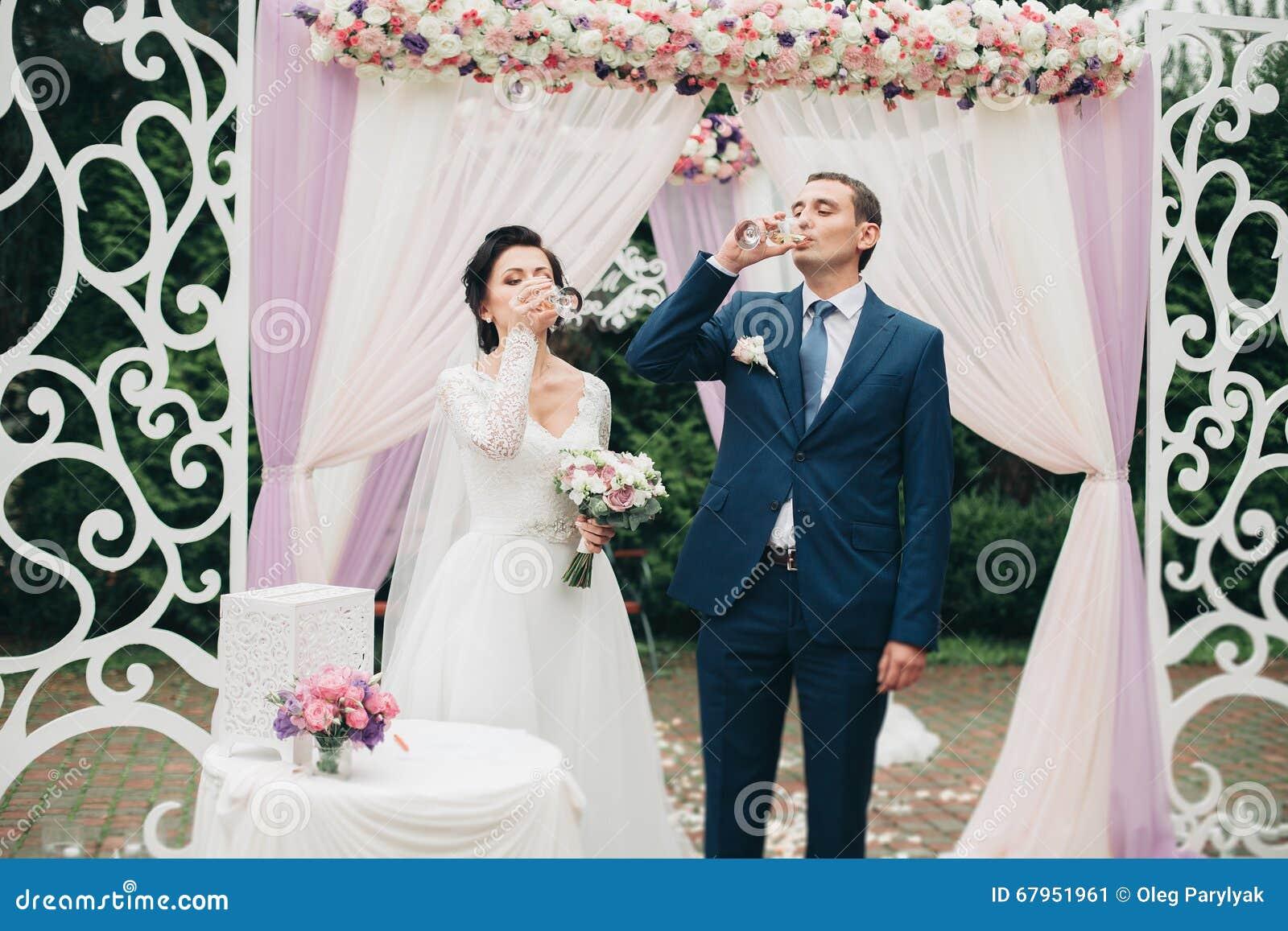 Huwelijkspaar die zich onder een boog van verse bloemen bevinden