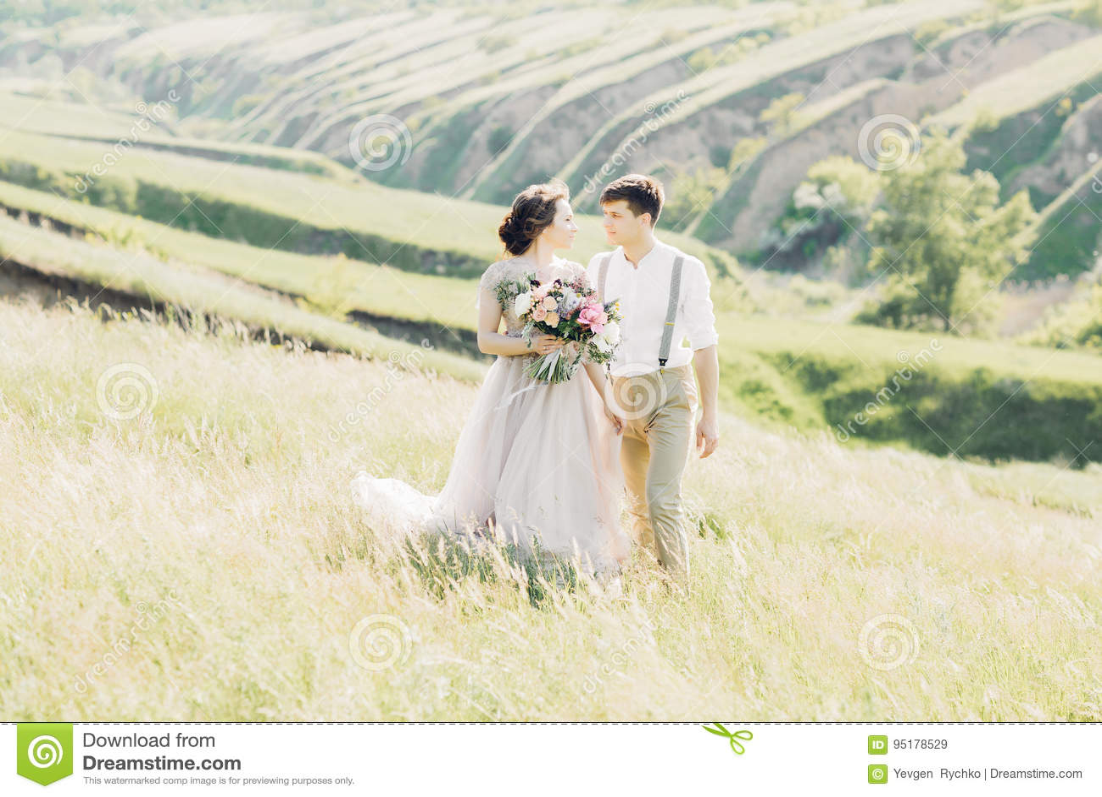 Huwelijkspaar op aard bruid en bruidegom die bij huwelijk koesteren