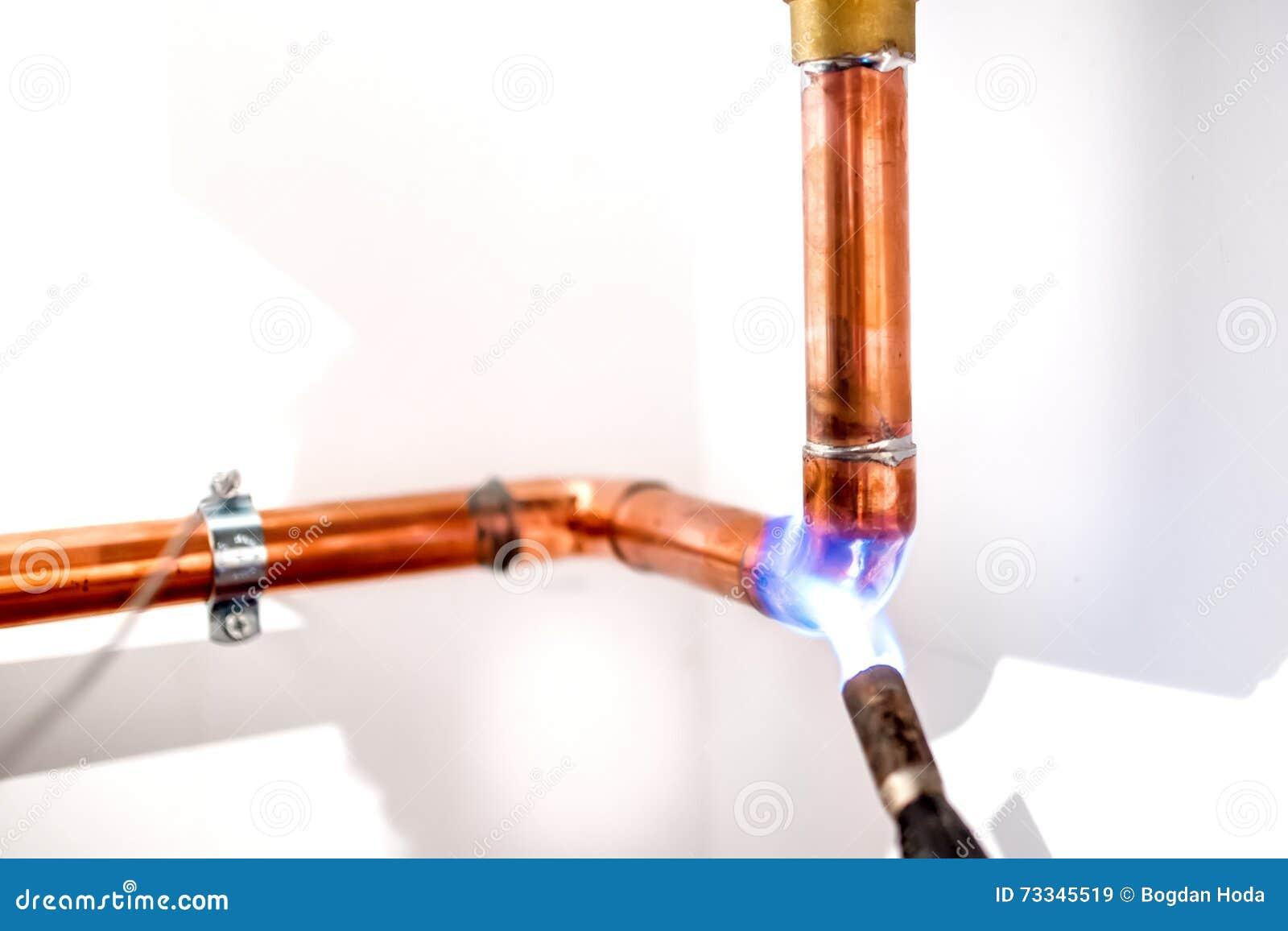 Hydraulik używa blowtorch, propanu gazu pochodnia dla spawać miedziane drymby