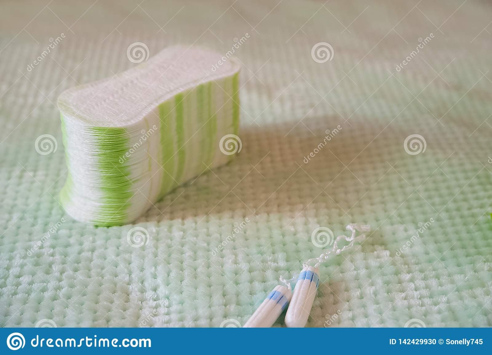 Hygienic tampons and pads on a textured turquoise background. Means of female intimate hygiene close-up and copy space