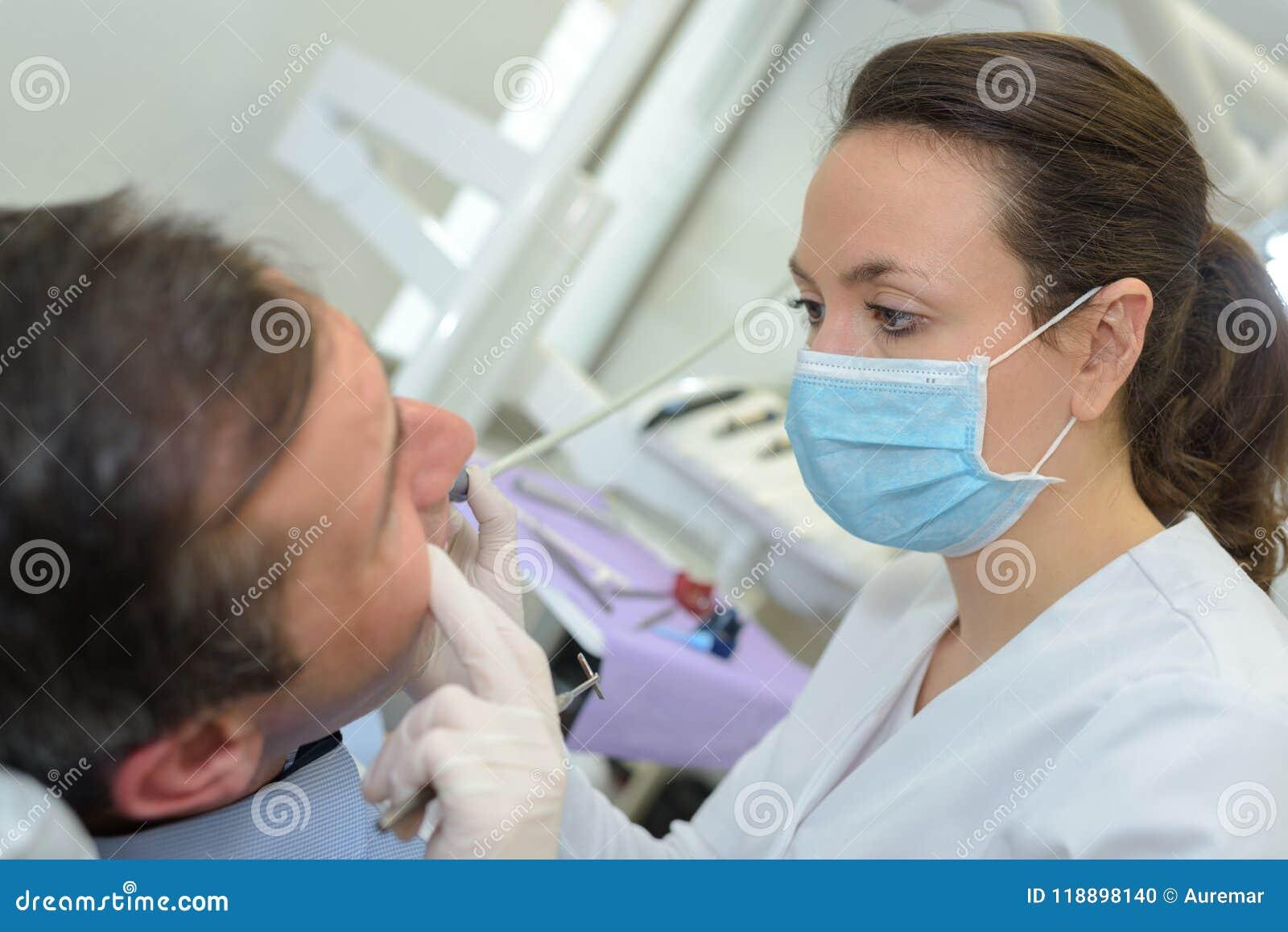 Hygieniker, der an Mann ` s Zähnen arbeitet