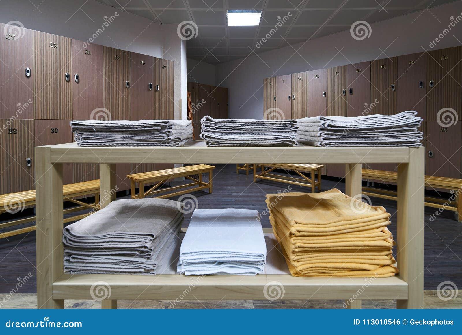 Hylla för rena handdukar i en omklädningsrum med låsbara skåp med träbänkar i luxur
