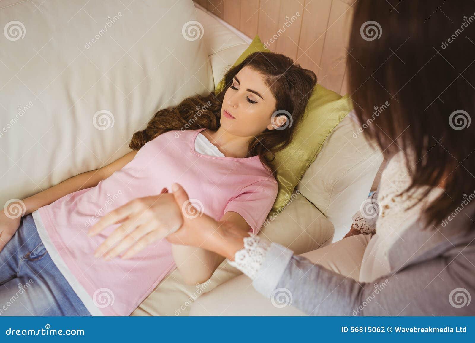 Hypnotherapist trzyma jej pacjenta nadgarstek