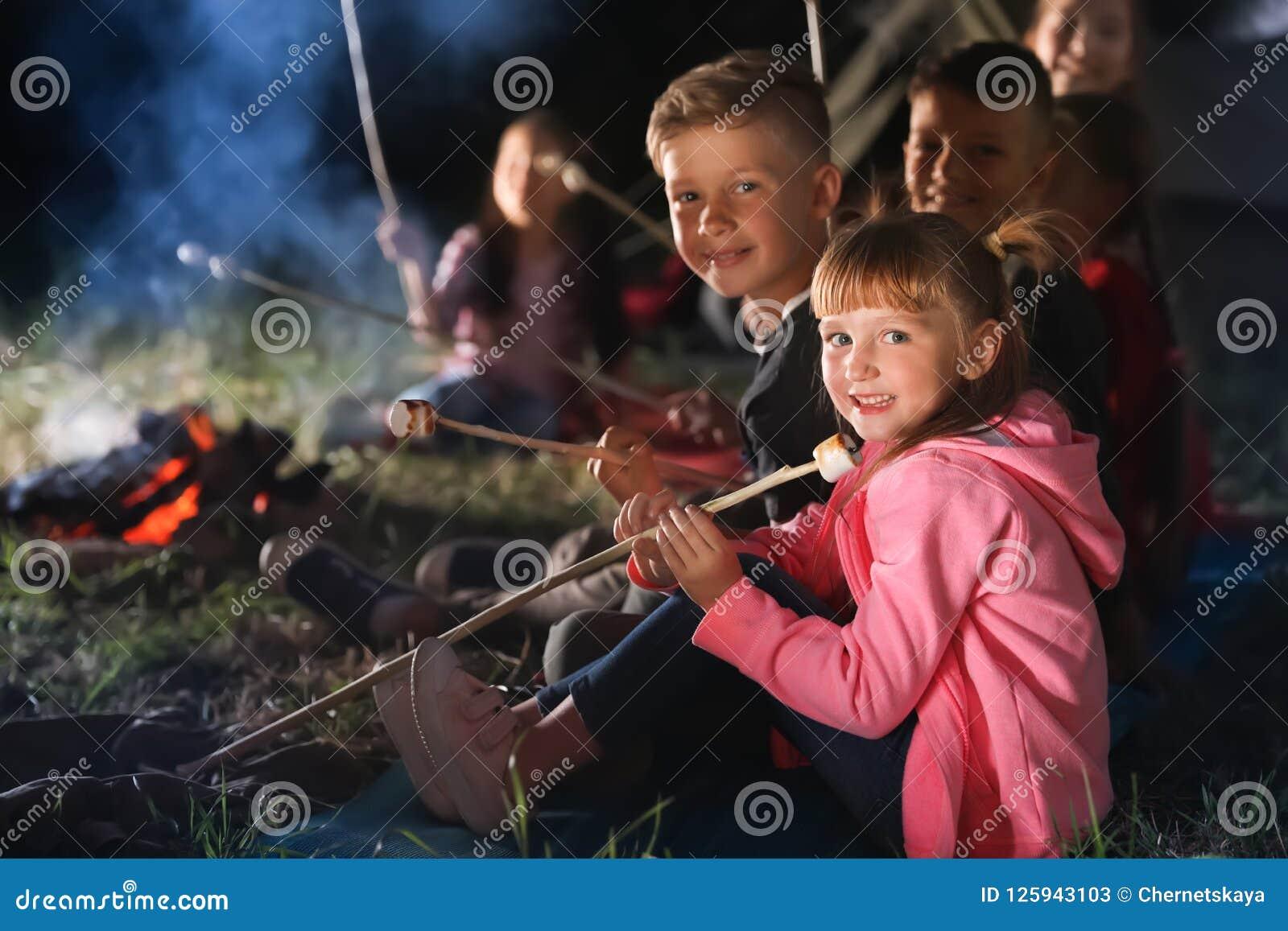 I bambini con le caramelle gommosa e molle si avvicinano al falò alla notte