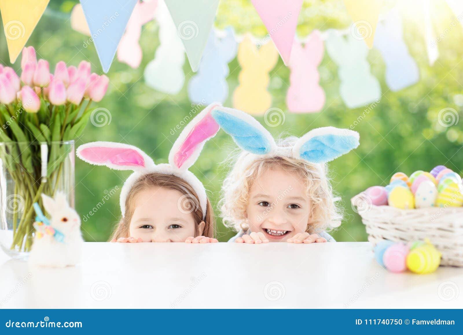 I bambini con le orecchie e le uova del coniglietto sull uovo di Pasqua cercano