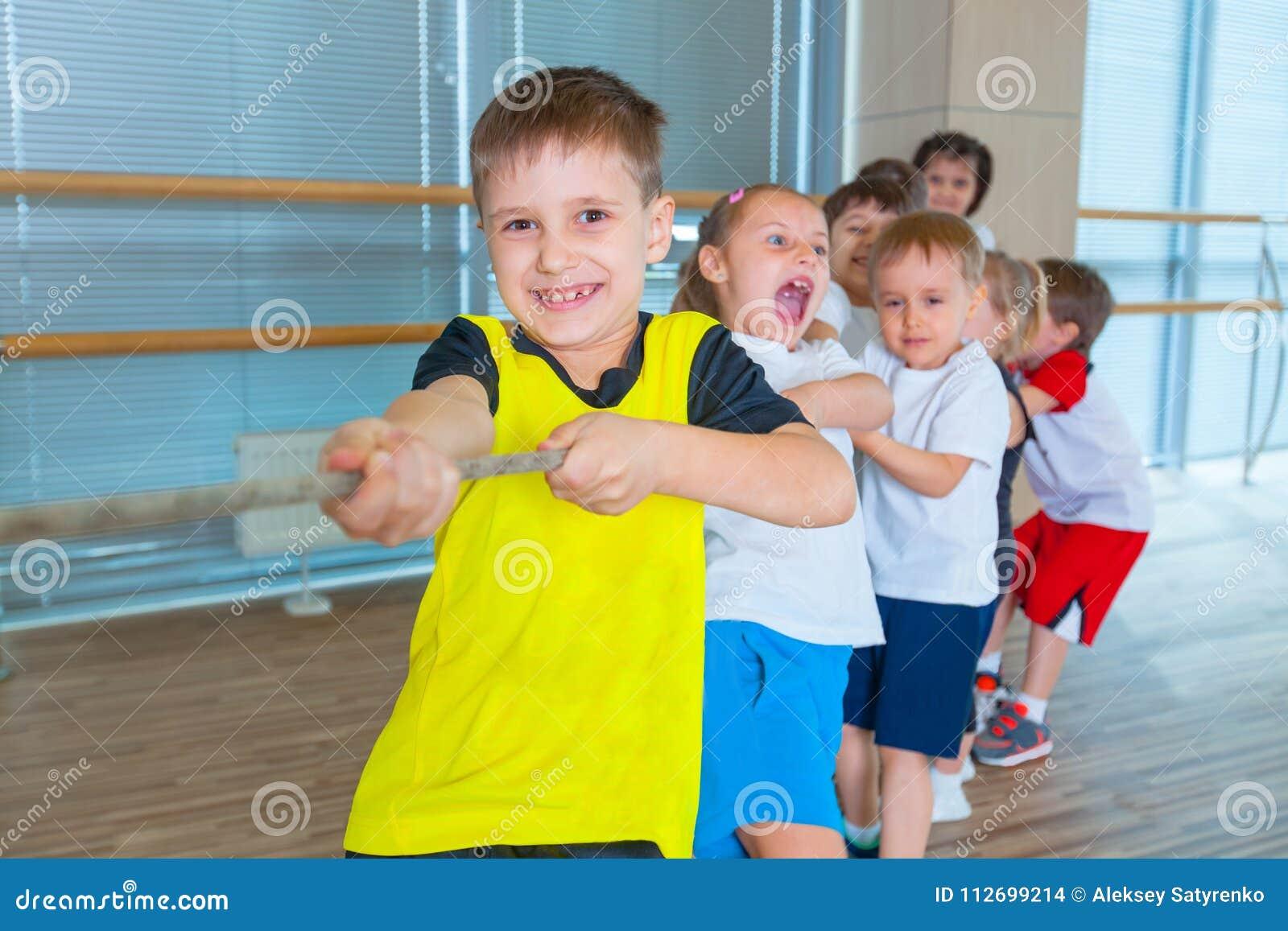 I bambini e la ricreazione, gruppo di scuola multietnica felice scherza il gioco del conflitto con la corda in palestra
