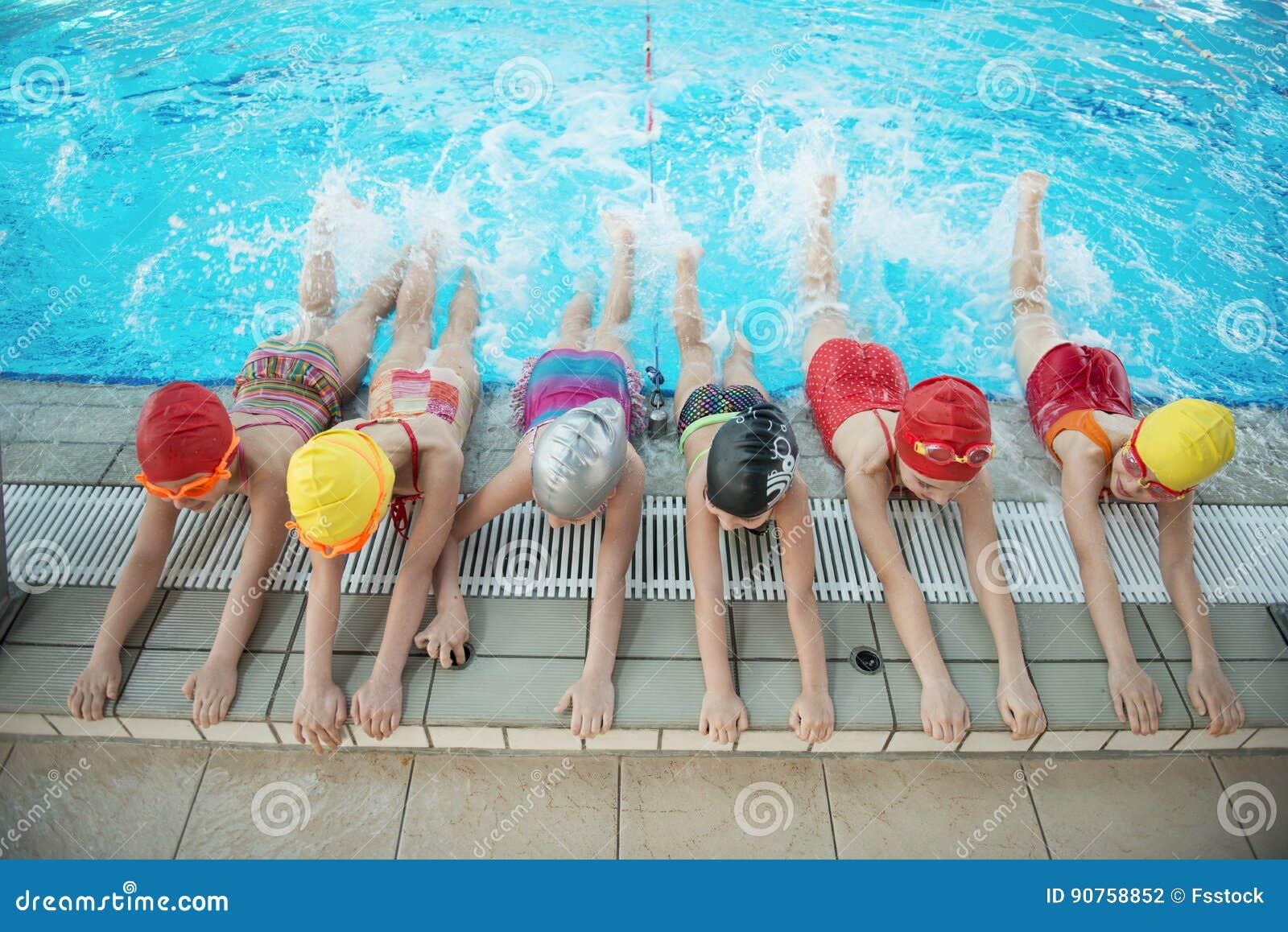 I bambini felici scherza il gruppo alla classe della piscina che impara nuotare