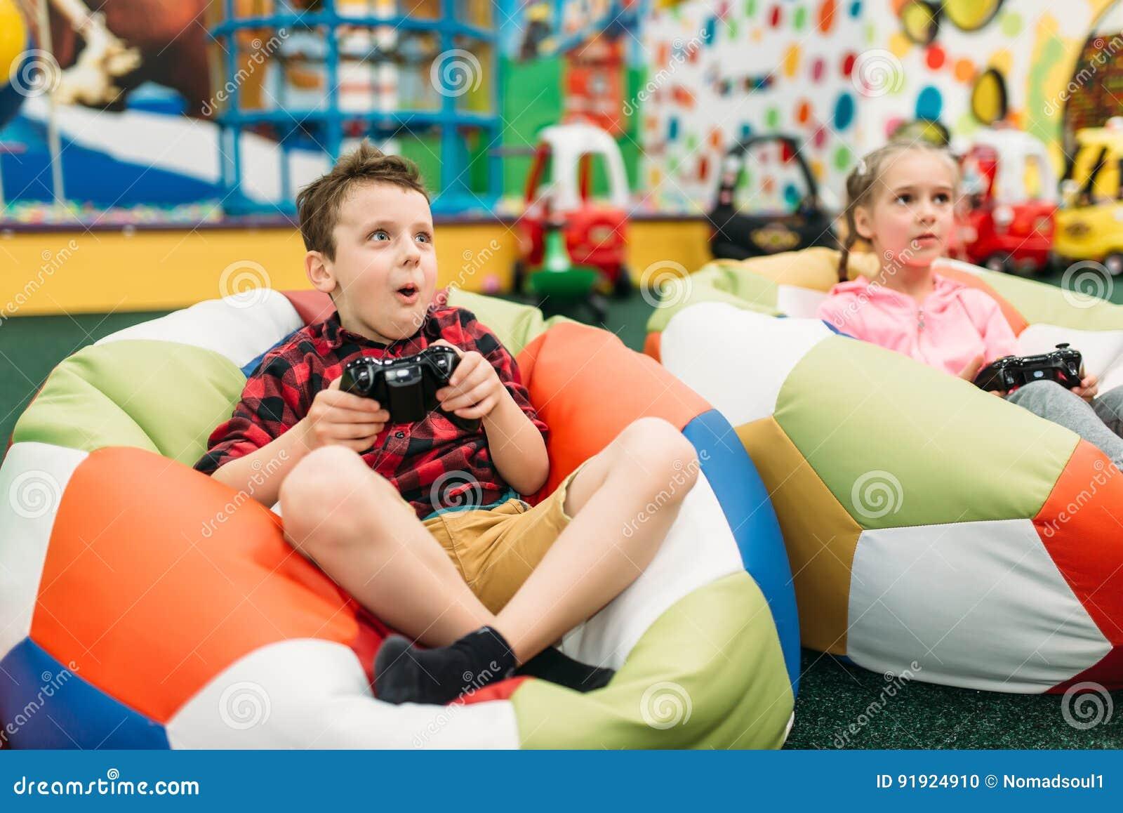 I bambini giocano in una console dei giochi, infanzia felice