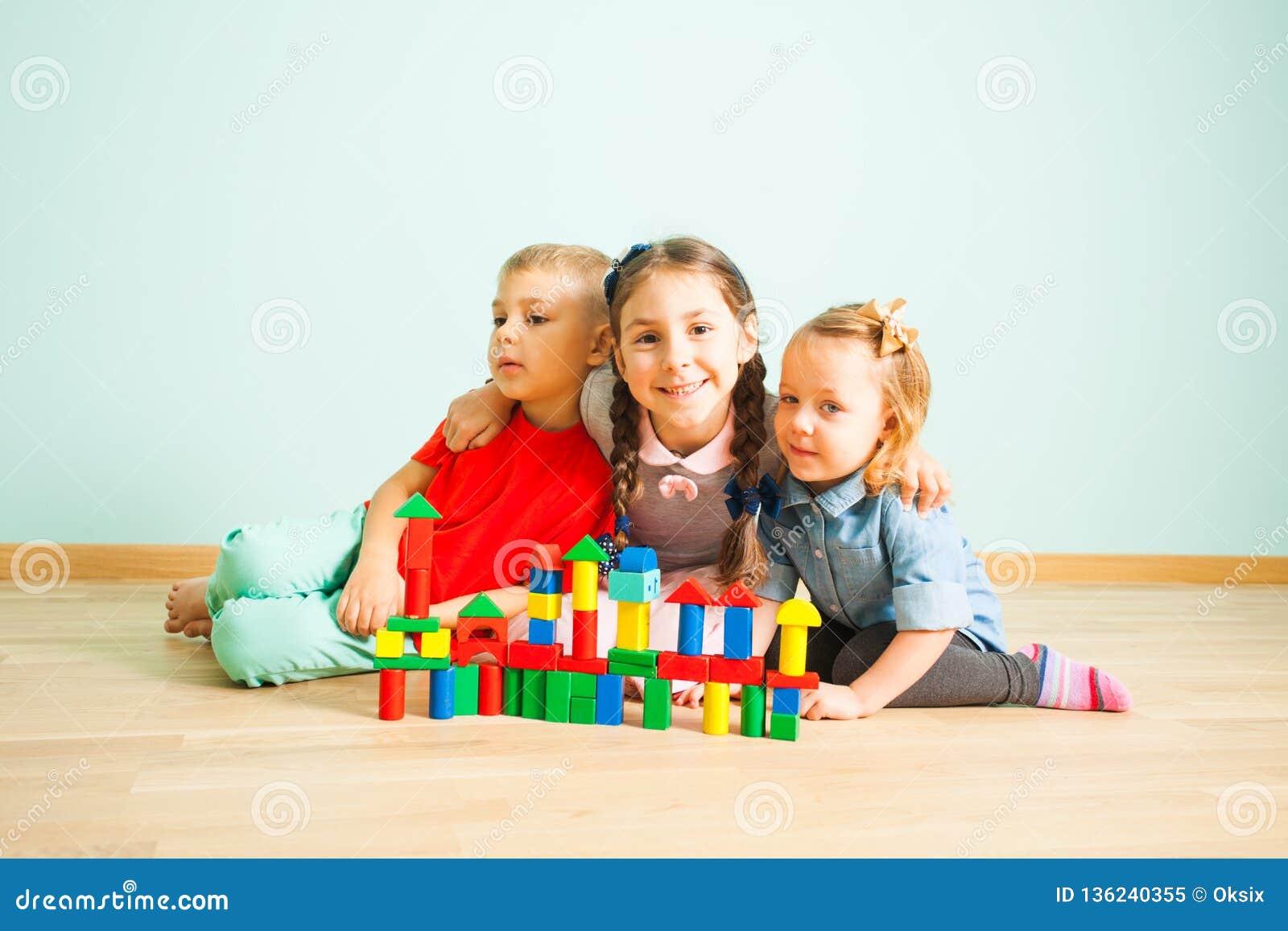 I bambini sorridenti felici dietro i blocchi di legno fortificano
